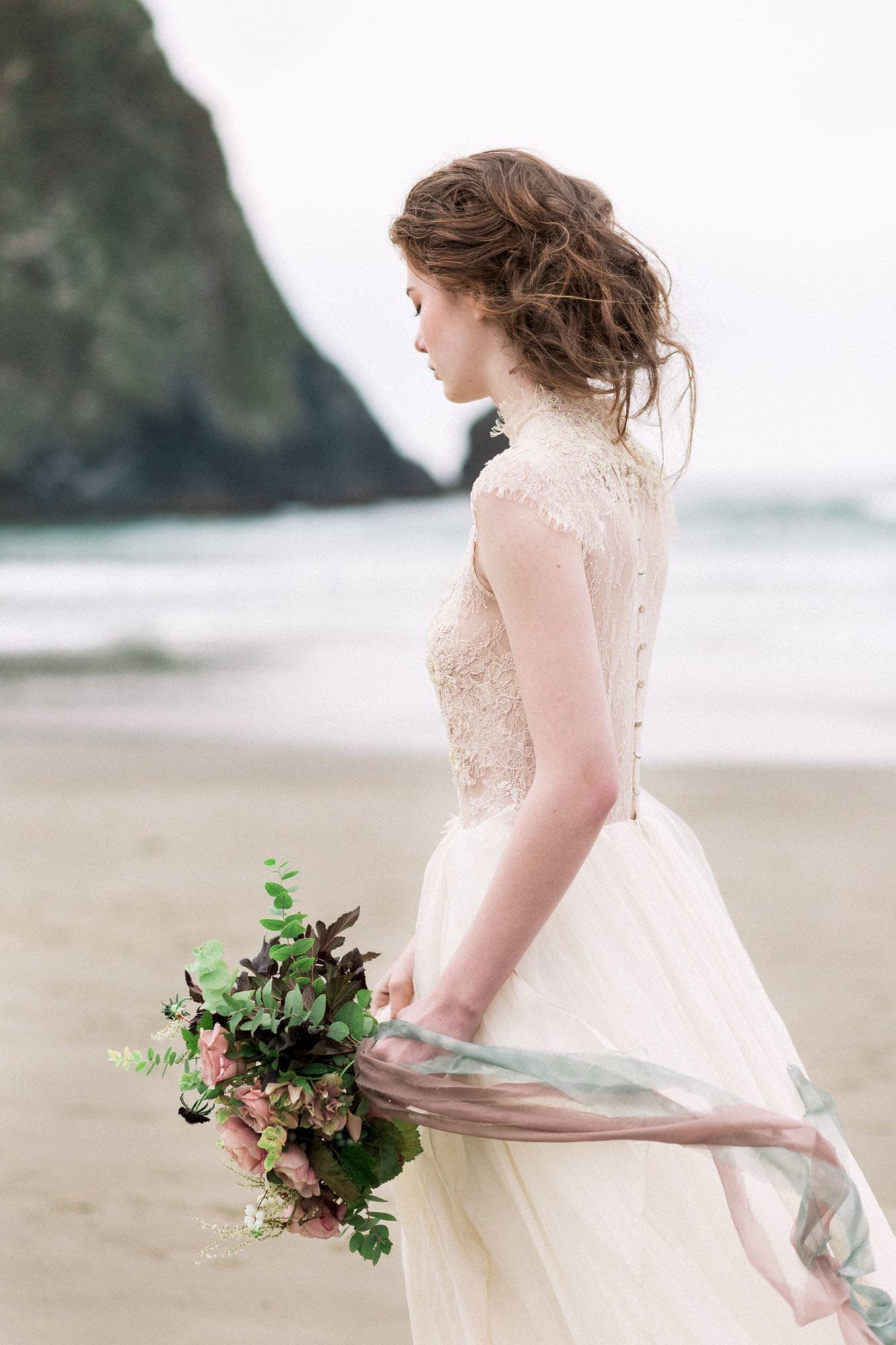 Bride at Cannon Beach during a rainy Oregon coast elopement