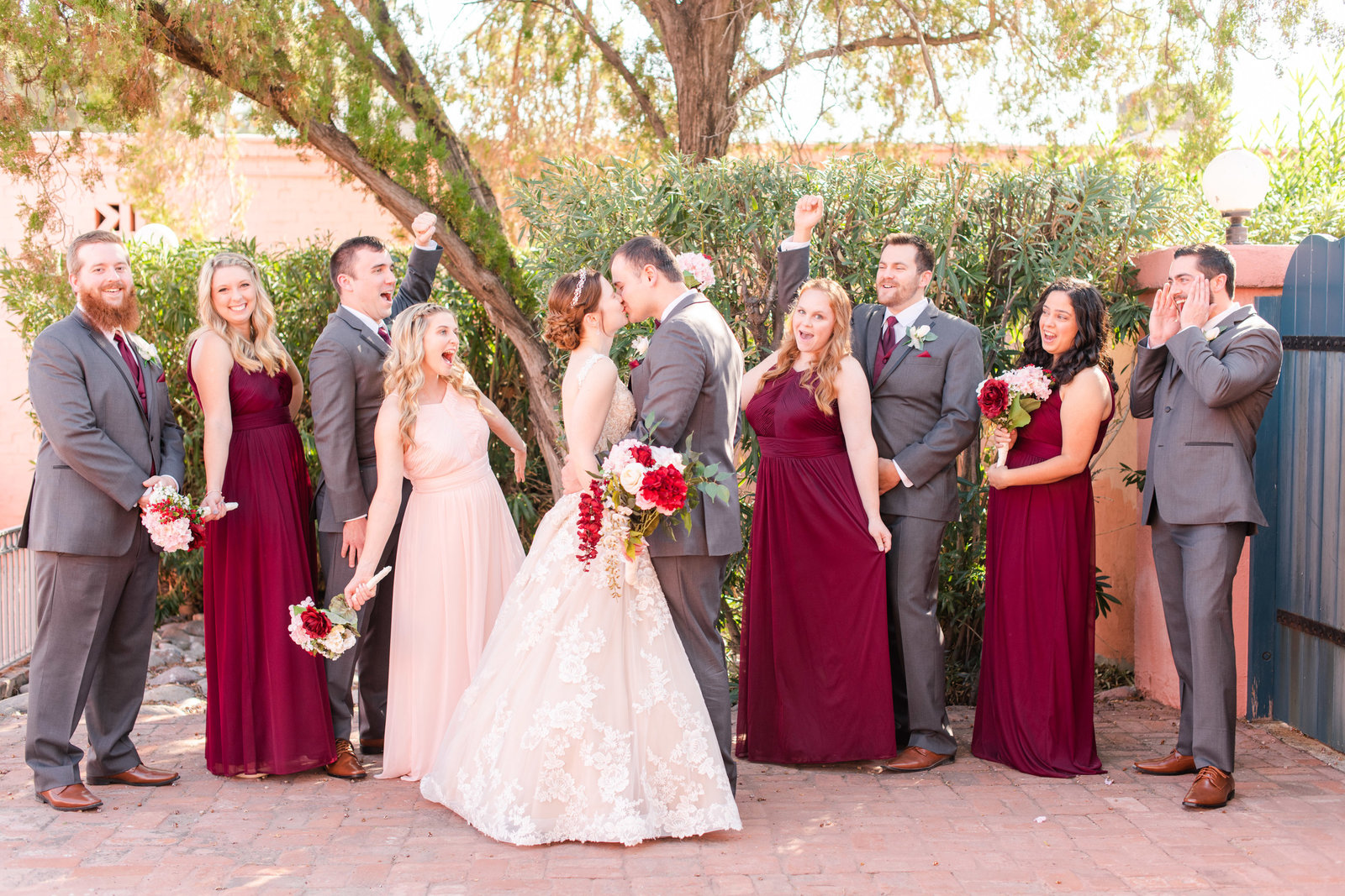 wedding couple kissing and bridal party celebrating