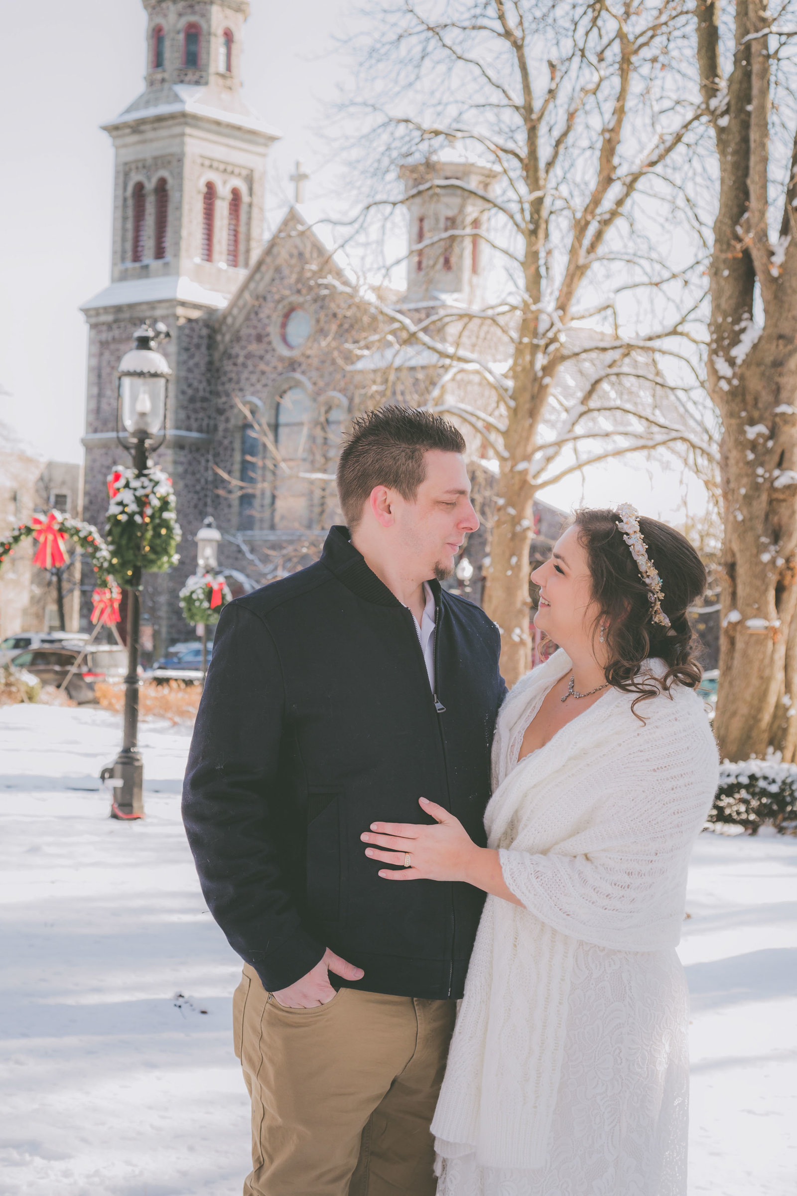 Couple looks at each other while NJ church in background on a snow covered day.