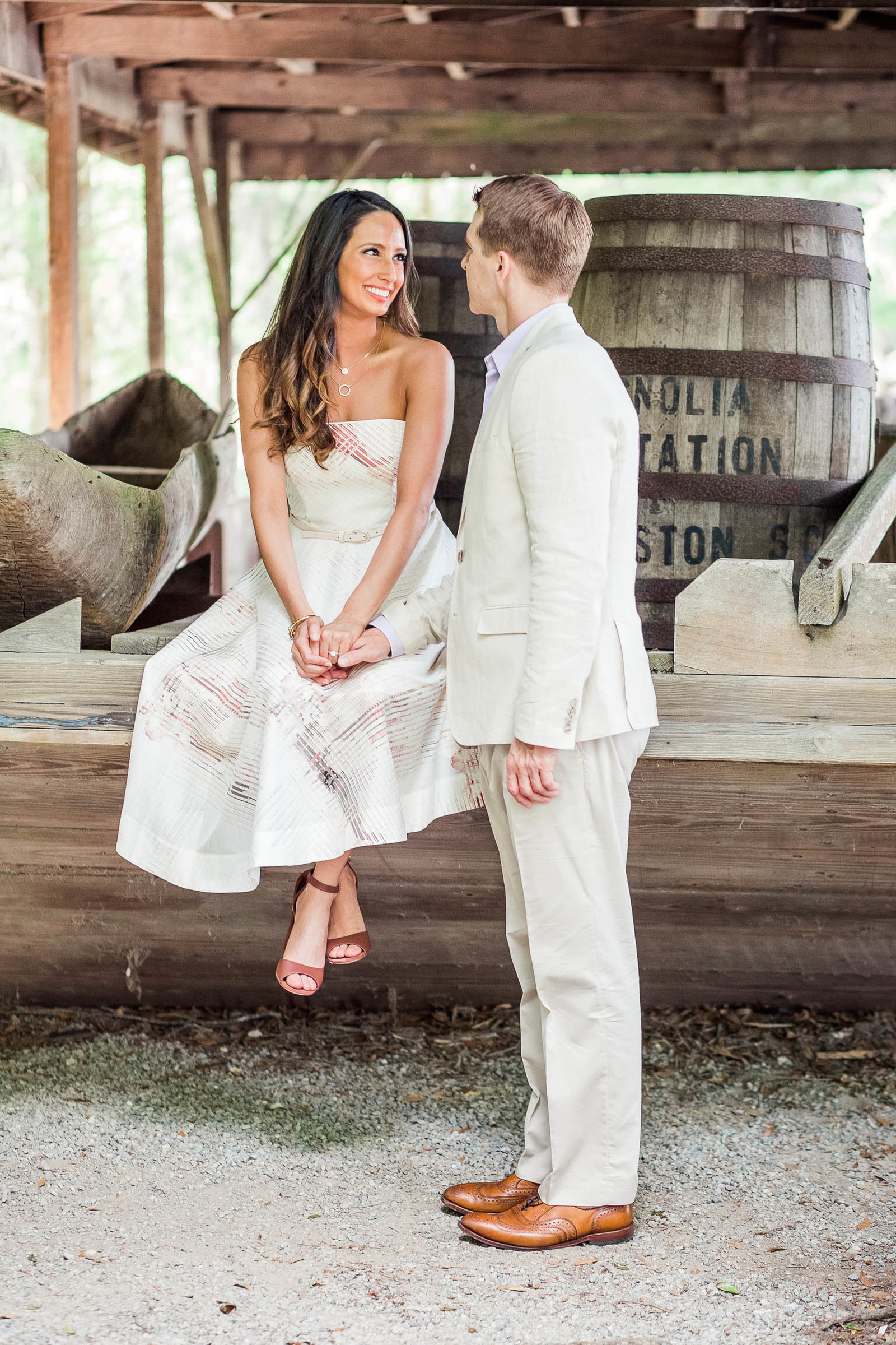 Engaged couple pose by old boat and barrels, Magnolia Plantation, Charleston, South Carolina