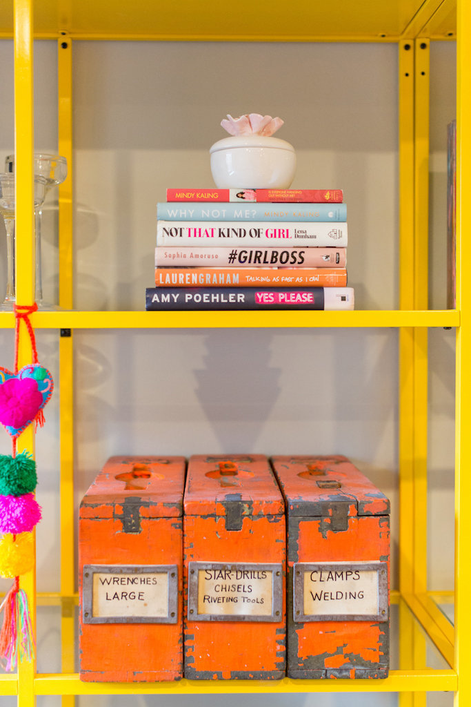 Yellow and glass shelve with orange canisters and a stack of books.