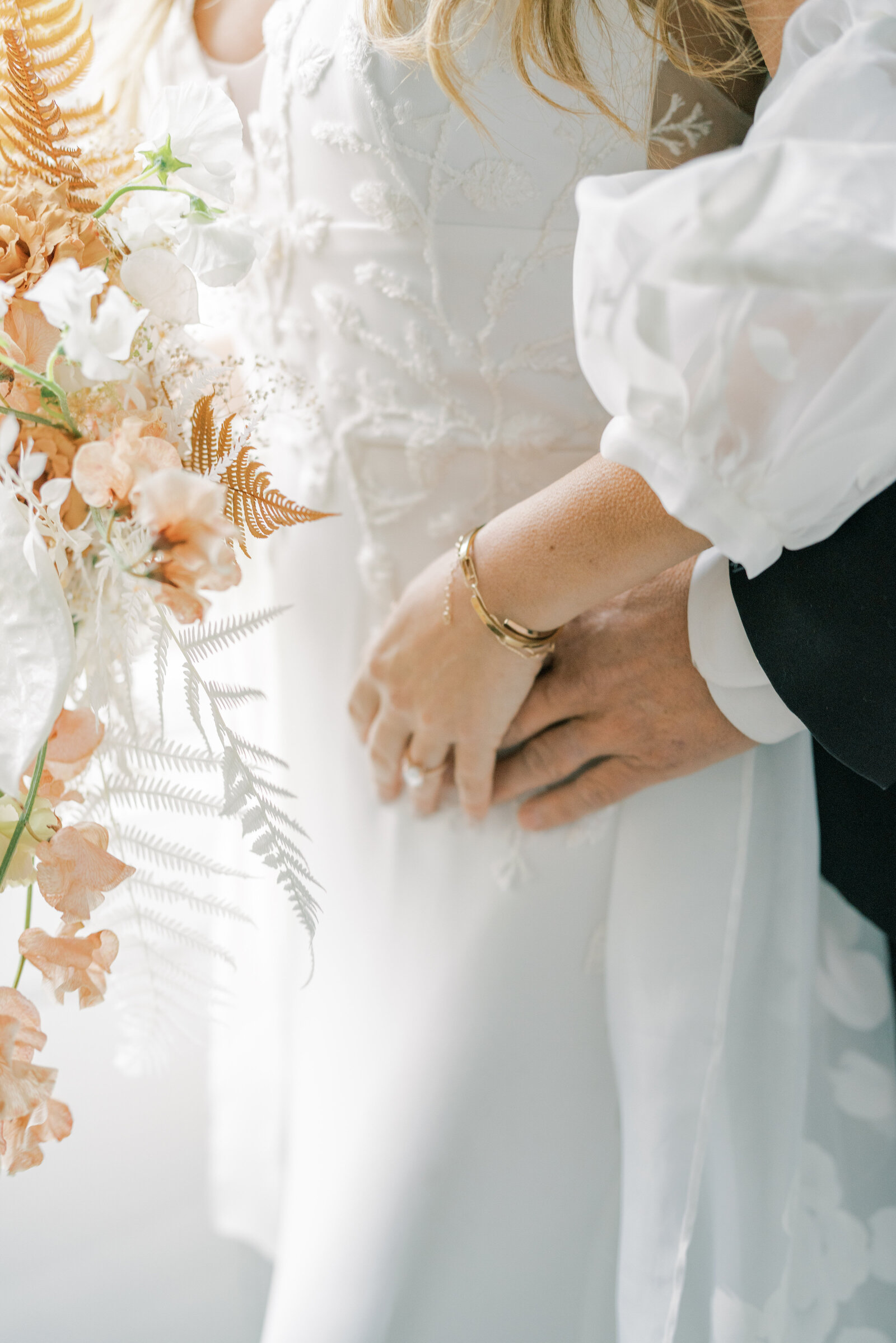 bride and groom holding hands with with bouquet