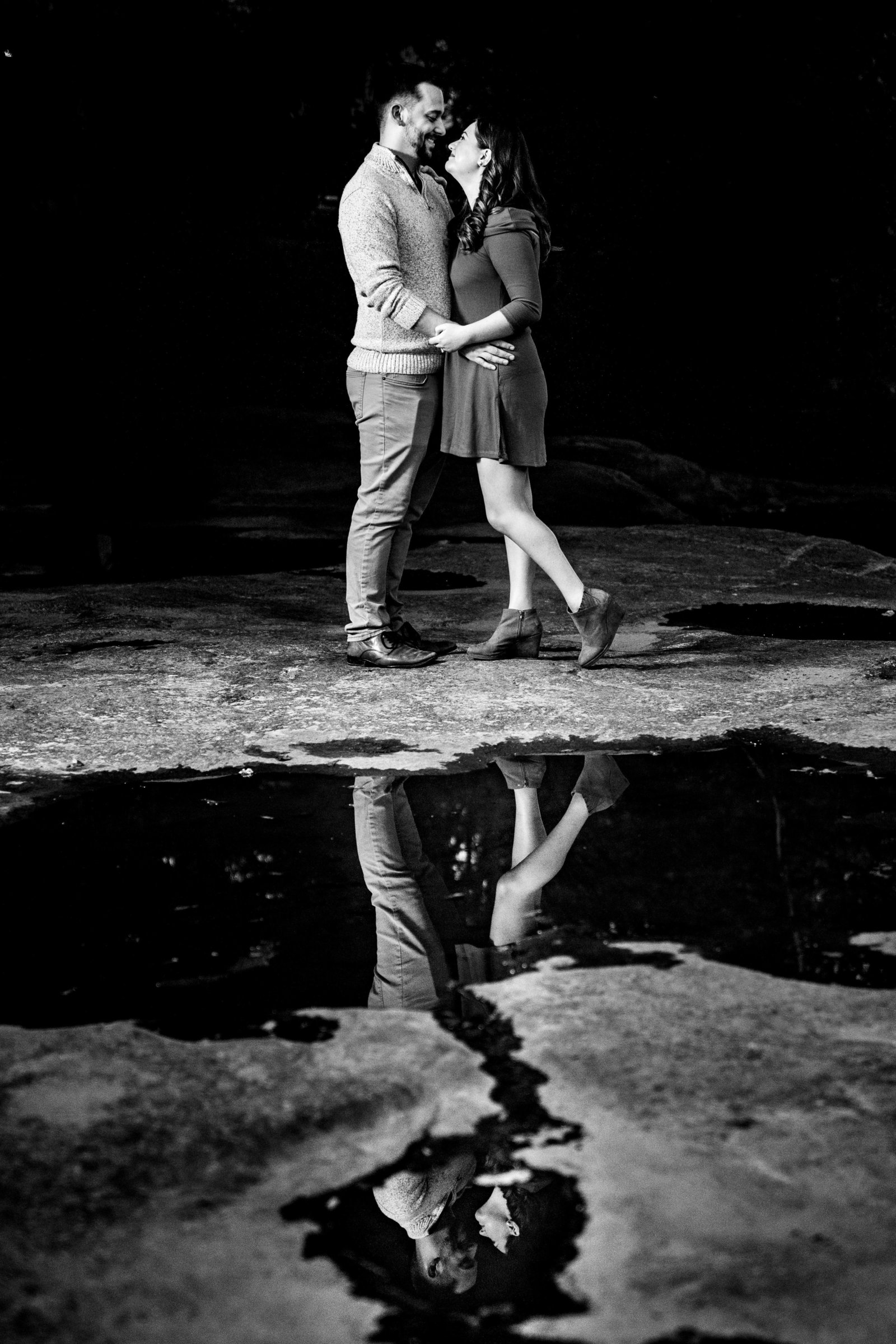 couple standing near puddle with reflection