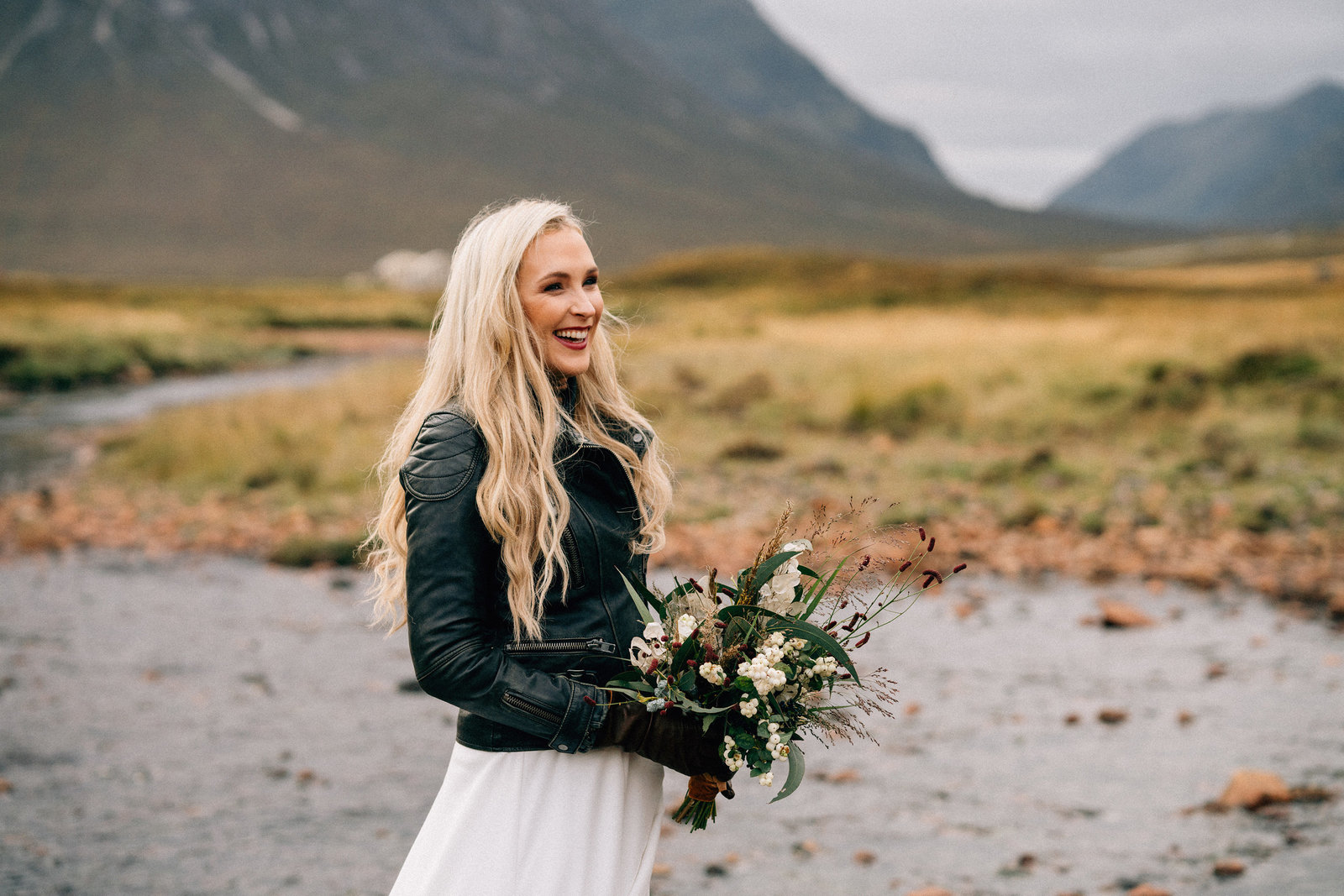 Blonde bride smiling before her ceremony, holding her bouquet in Glencoe, the Scottish Highlands