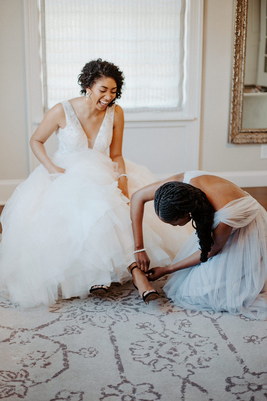 Bridesmaid helping the bride put on her shoes  during his Minneapolis wedding day