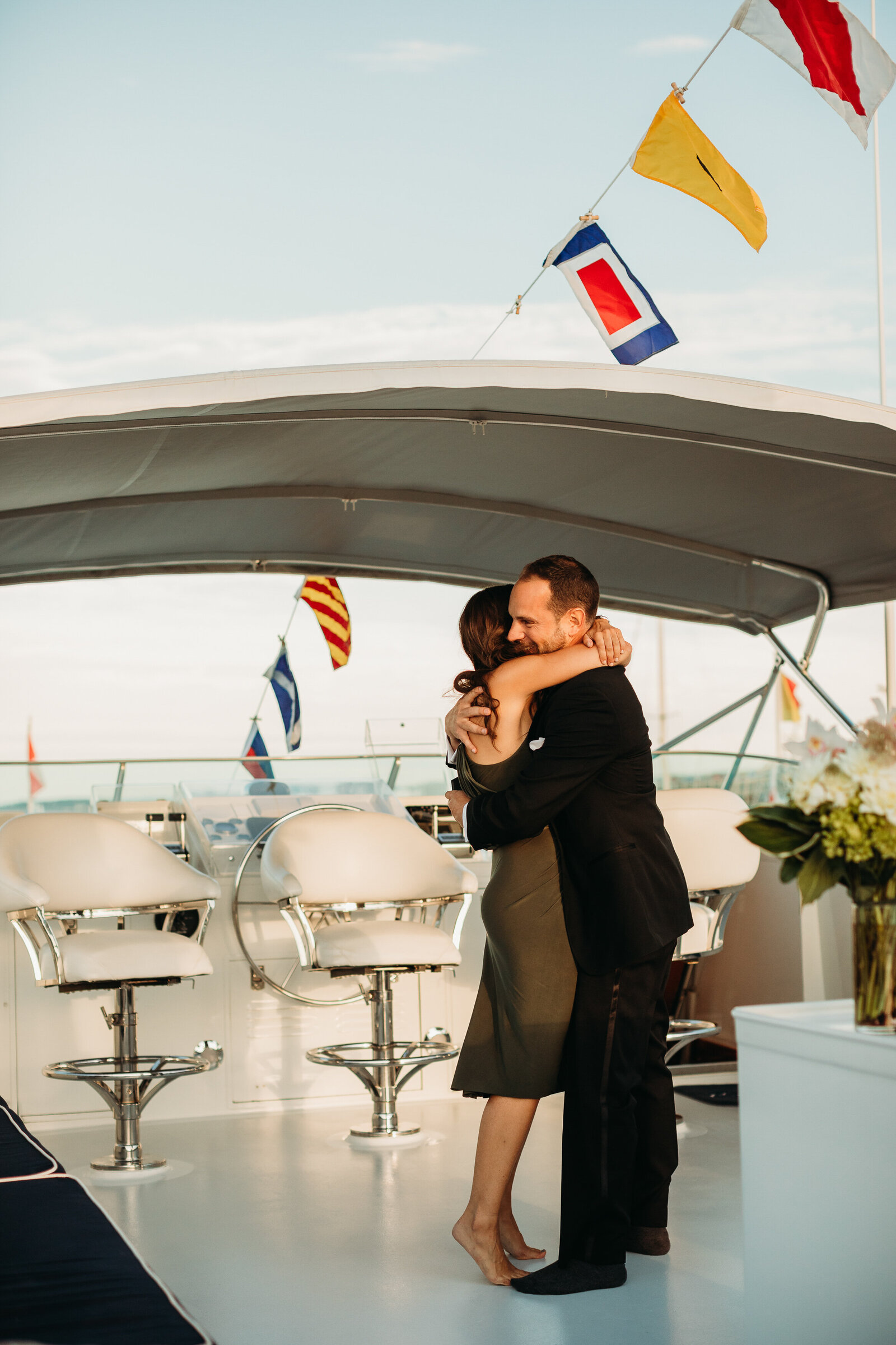couple embrace after proposal onboard a yacht