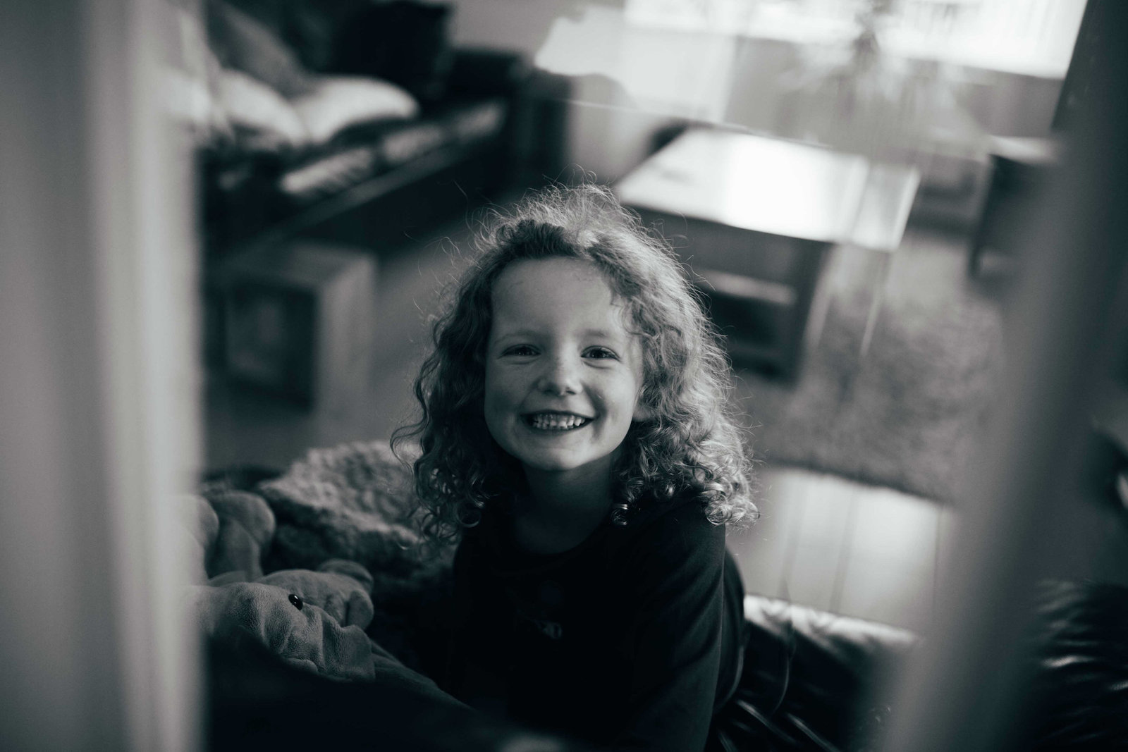 Black and white natural photograph of curly haired smiling Suffolk girl at home with family