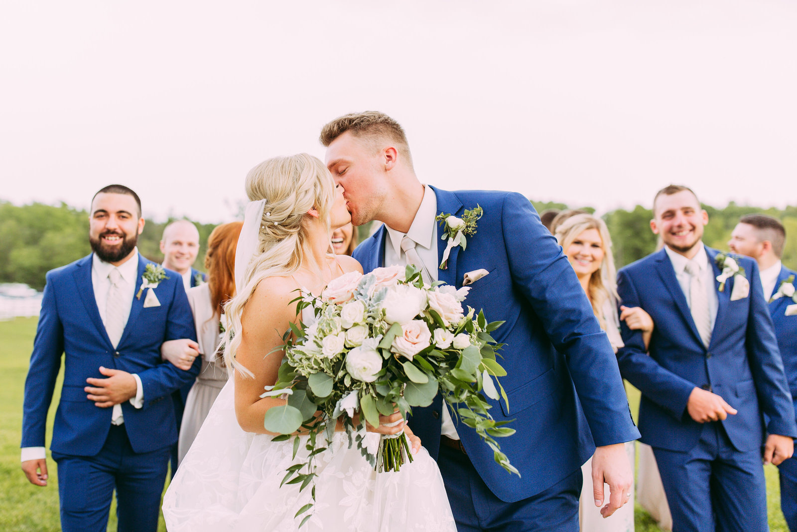 couple kissing at wedding with wedding party
