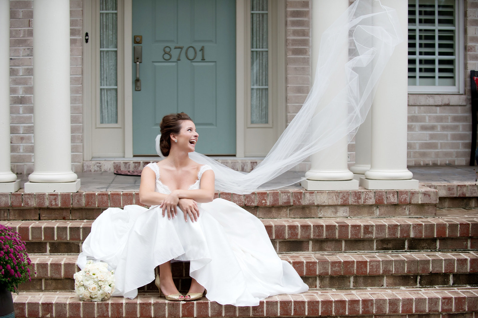 bride's veil flies up during a portrait on stairs