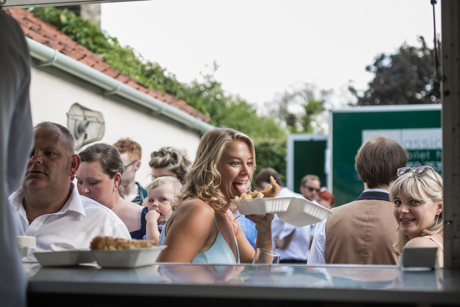A wedding guest is holding fish and chips and is sticking her tongue out at them whilst other guests queue up for fish and chips also at  a wedding in Norfolk.