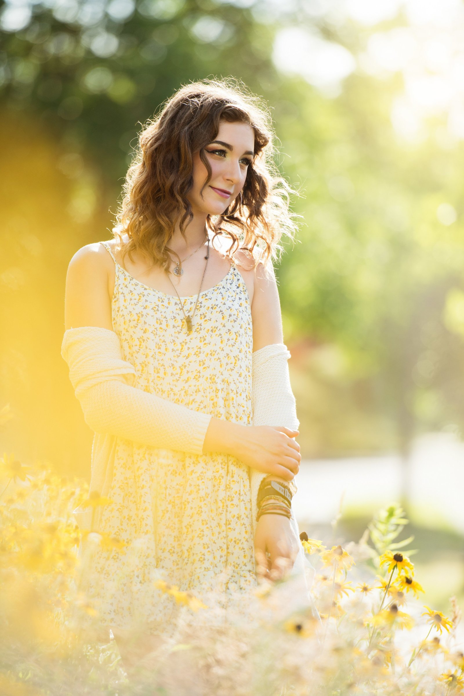 Glowing light senior picture of girl with curly hair and wildflowers