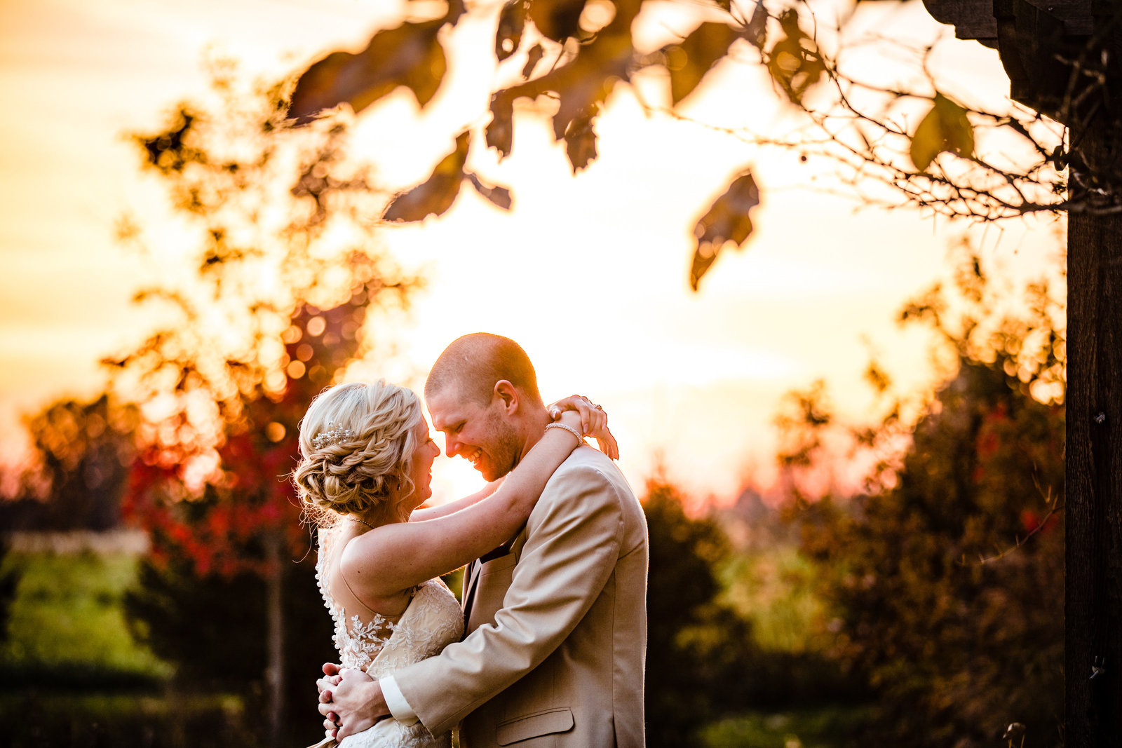 wedding photo of a bride and groom hugging in front of a sunset at Brookshire wedding venue