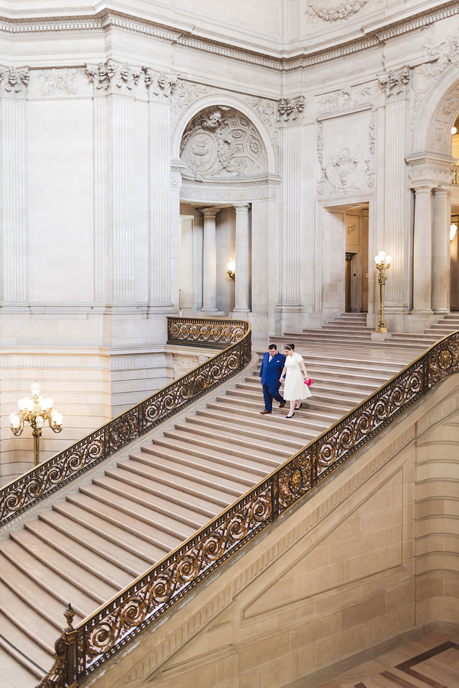 Couple descending the Grand Staircase on wedding day at San Francisco City Hall | Zoe Larkin Photography