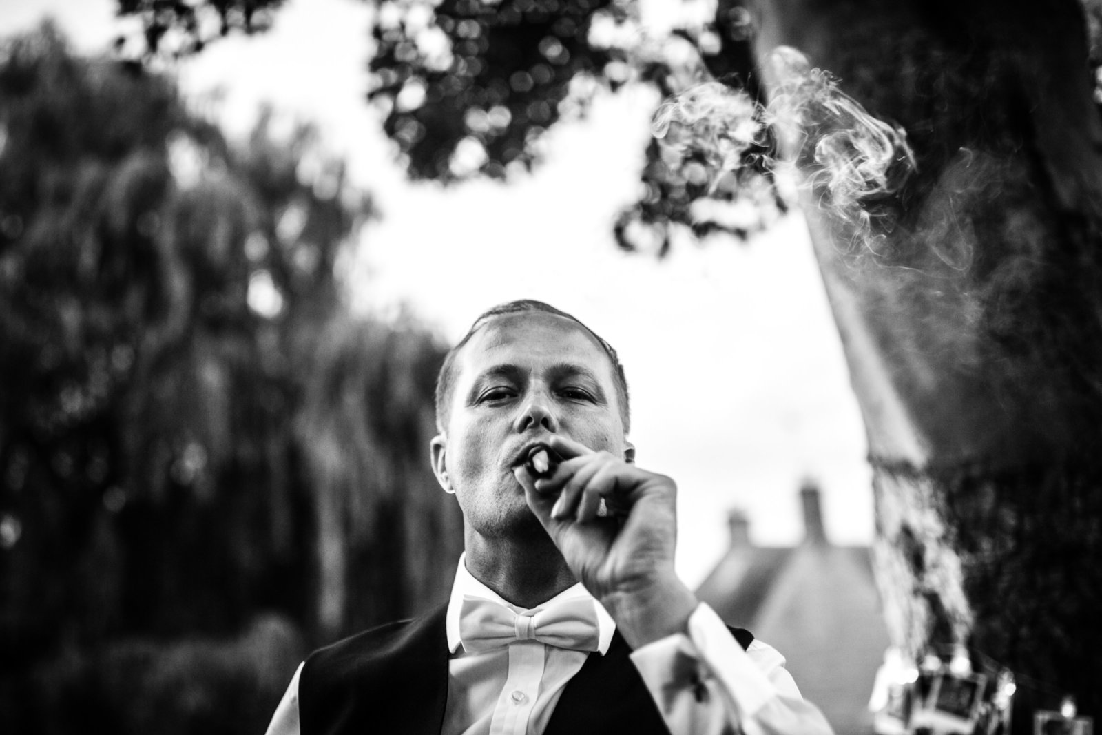A Groom smokes a cigar during the reception at his wedding