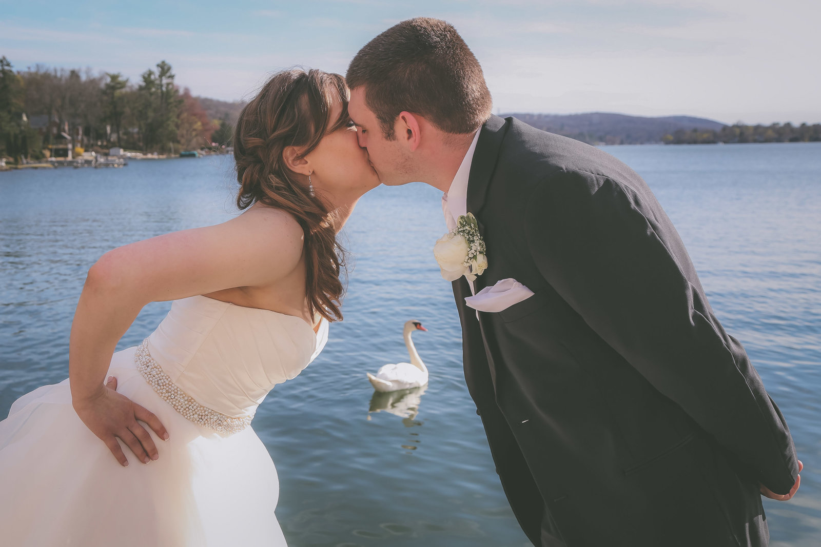 A couple kisses by a California lake with swan in between them.