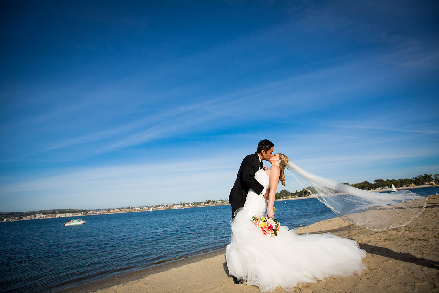 brides veil blowing in the wind bay in background