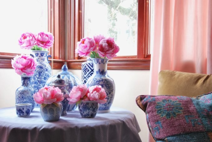 A round table with several blue and white vases with pink flowers.