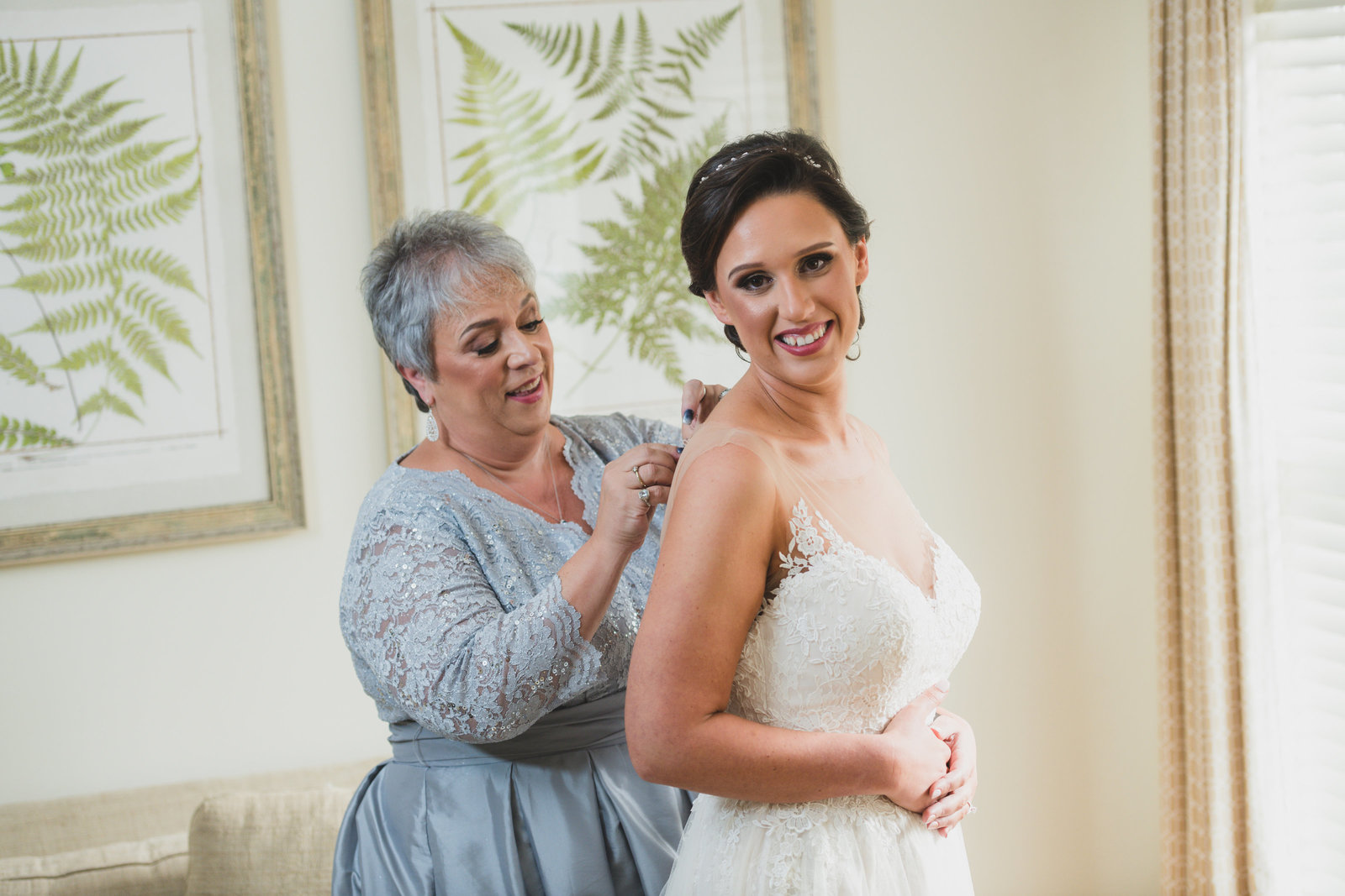 photo of mom helping bride with bridal dress from wedding at Three Village Inn