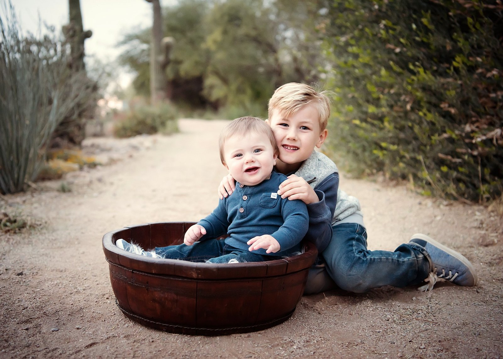 boy is hugging baby brother sitting in a bowl on the ground