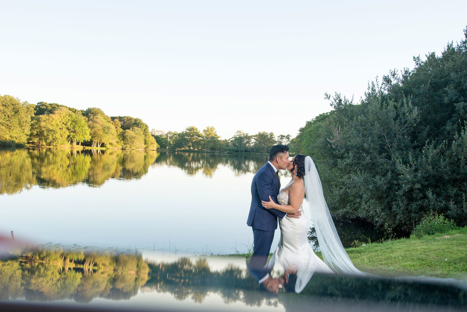 Bride and groom kissing by water at Camp Pa-Qua-Tuck