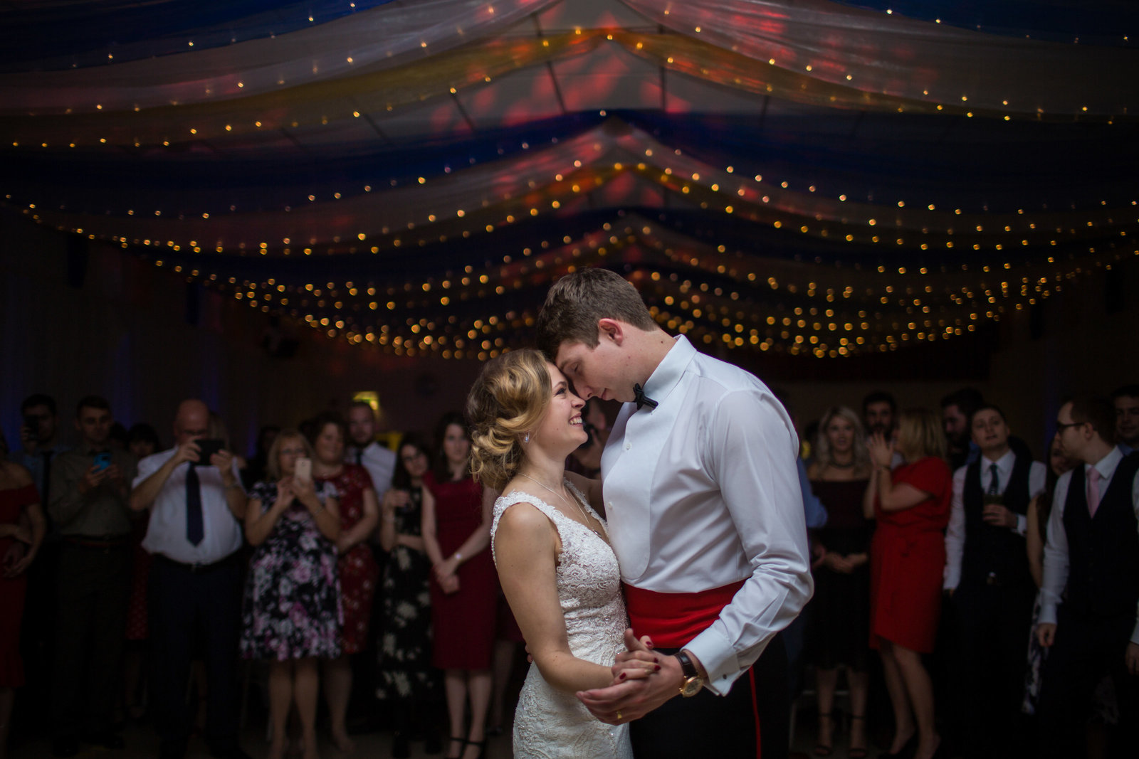 A bride and Groom hug closely during their first dance. The room is dimly lit with lighting on them only. They're surrounded by fairy lights.
