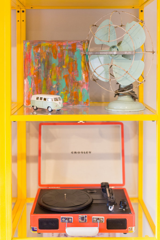Yellow and glass shelves with an orange record player, fan, art, and mini VW.