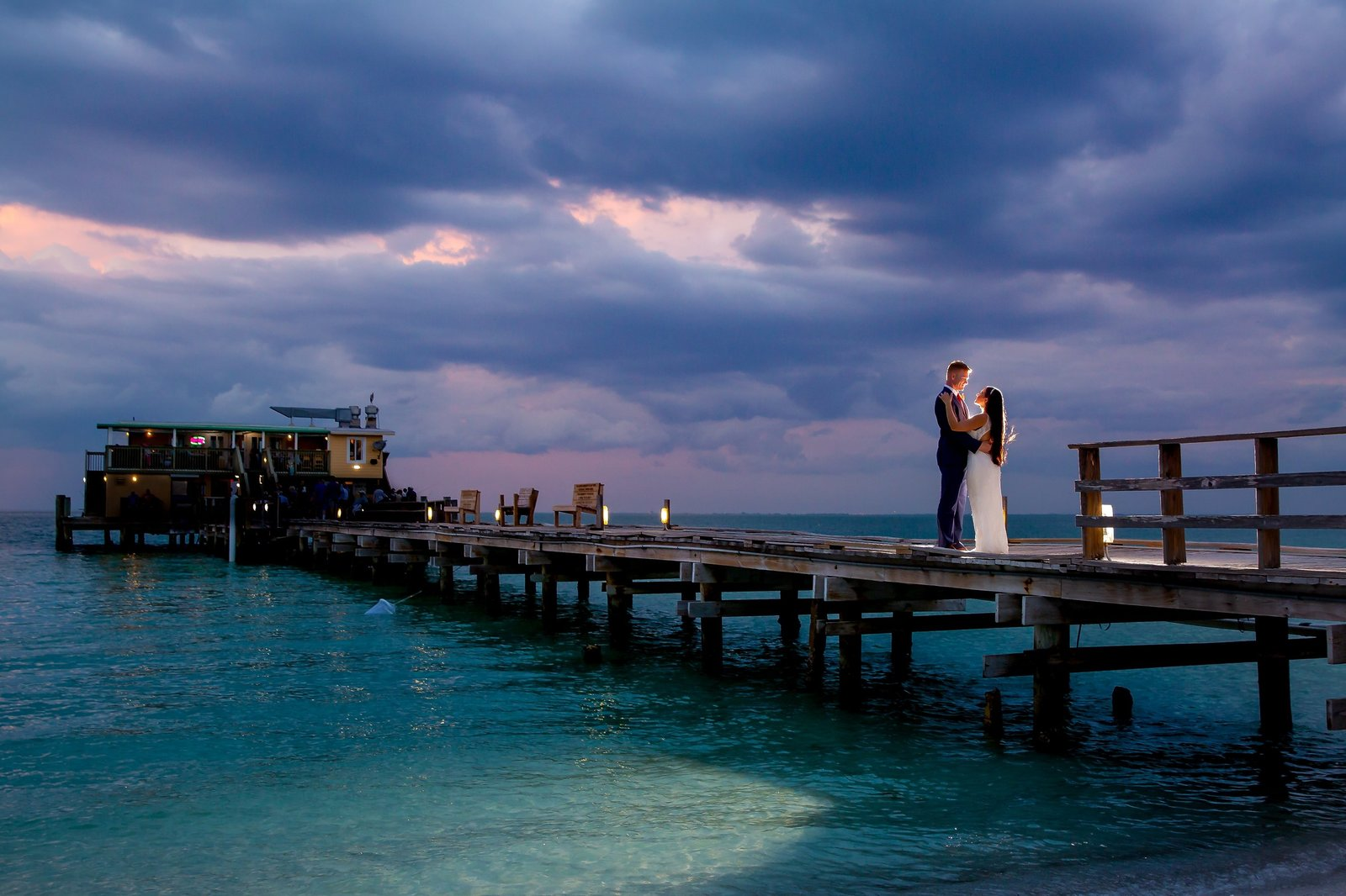 Wedding Photography at Rod and Reel Pier with bride and groom holding each other at sunset with backlight