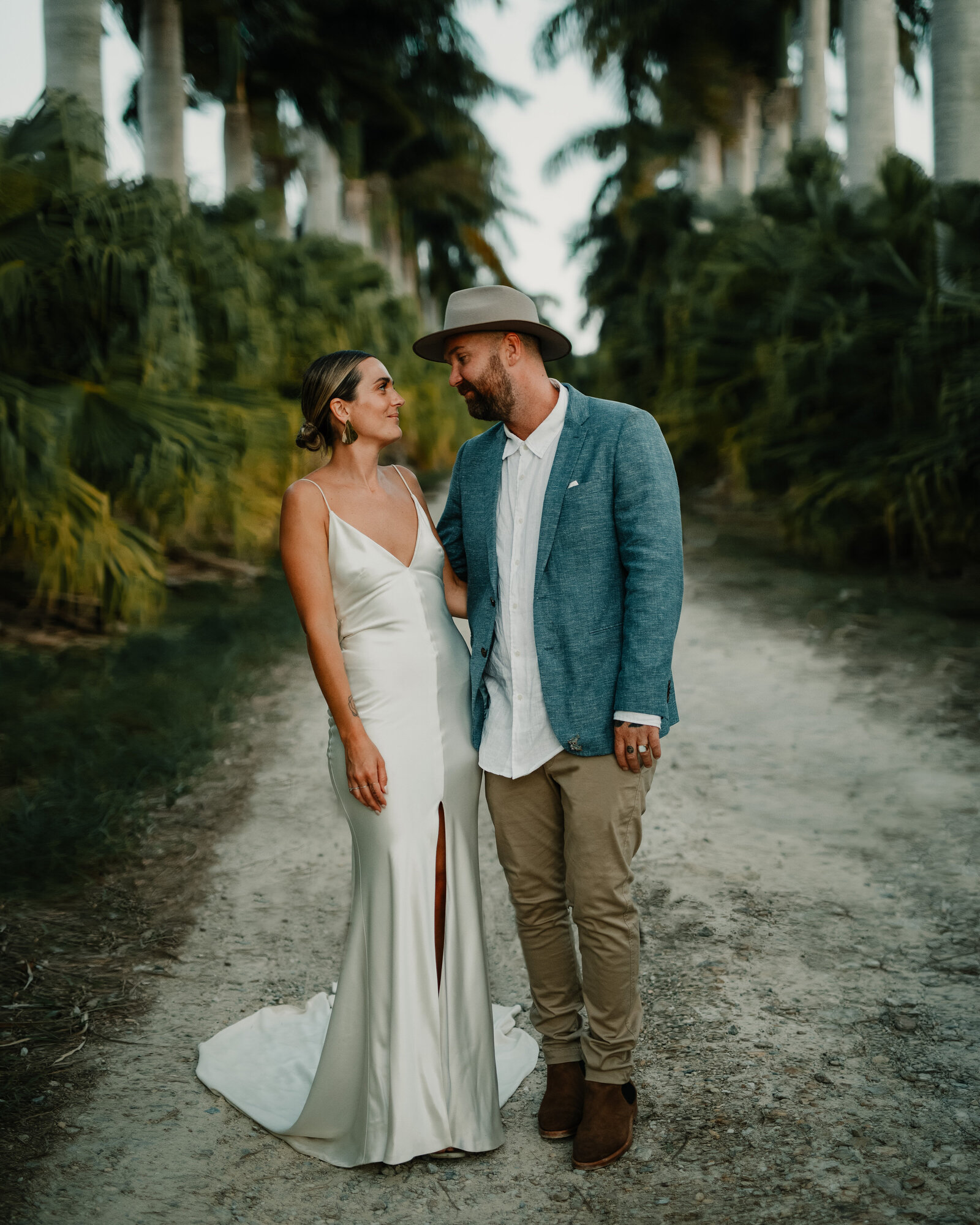married couple standing among palm trees