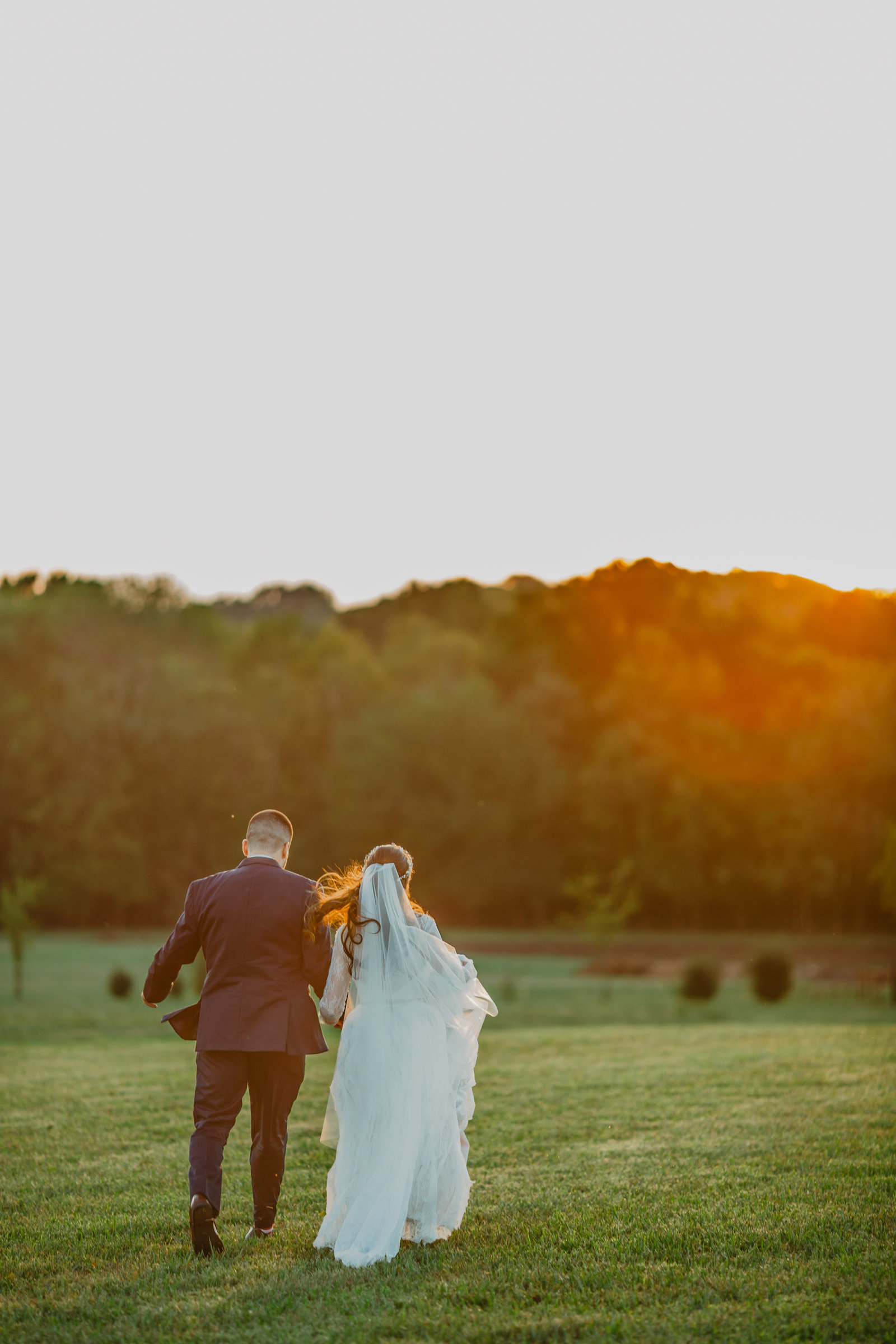During an epic sunset Bride and Groom run away holding hands at Allenbrooke Farm