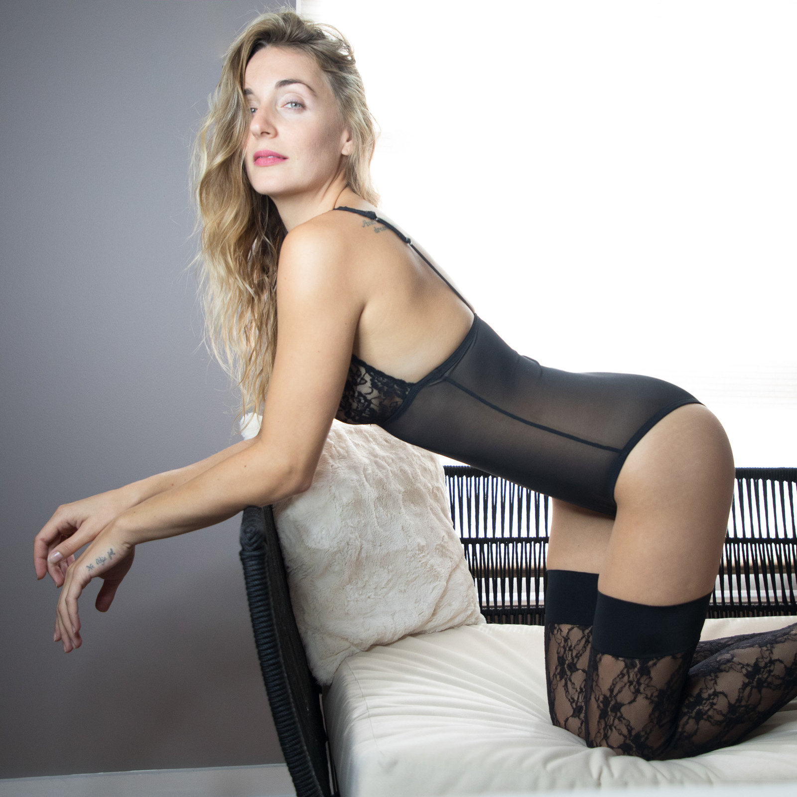 Celia arched over the couch in black lingerie and thigh high tights