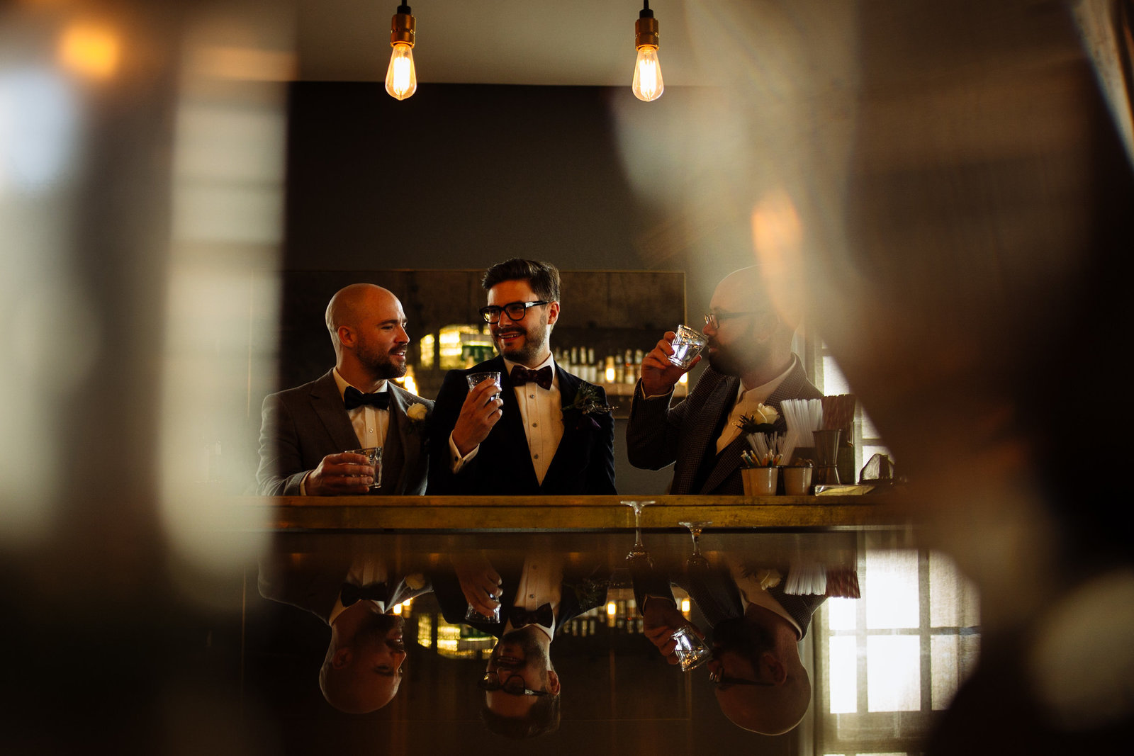 Cool groomsmen drinking in bar at Bethnall Green Town Hall Hotel. Modern photography