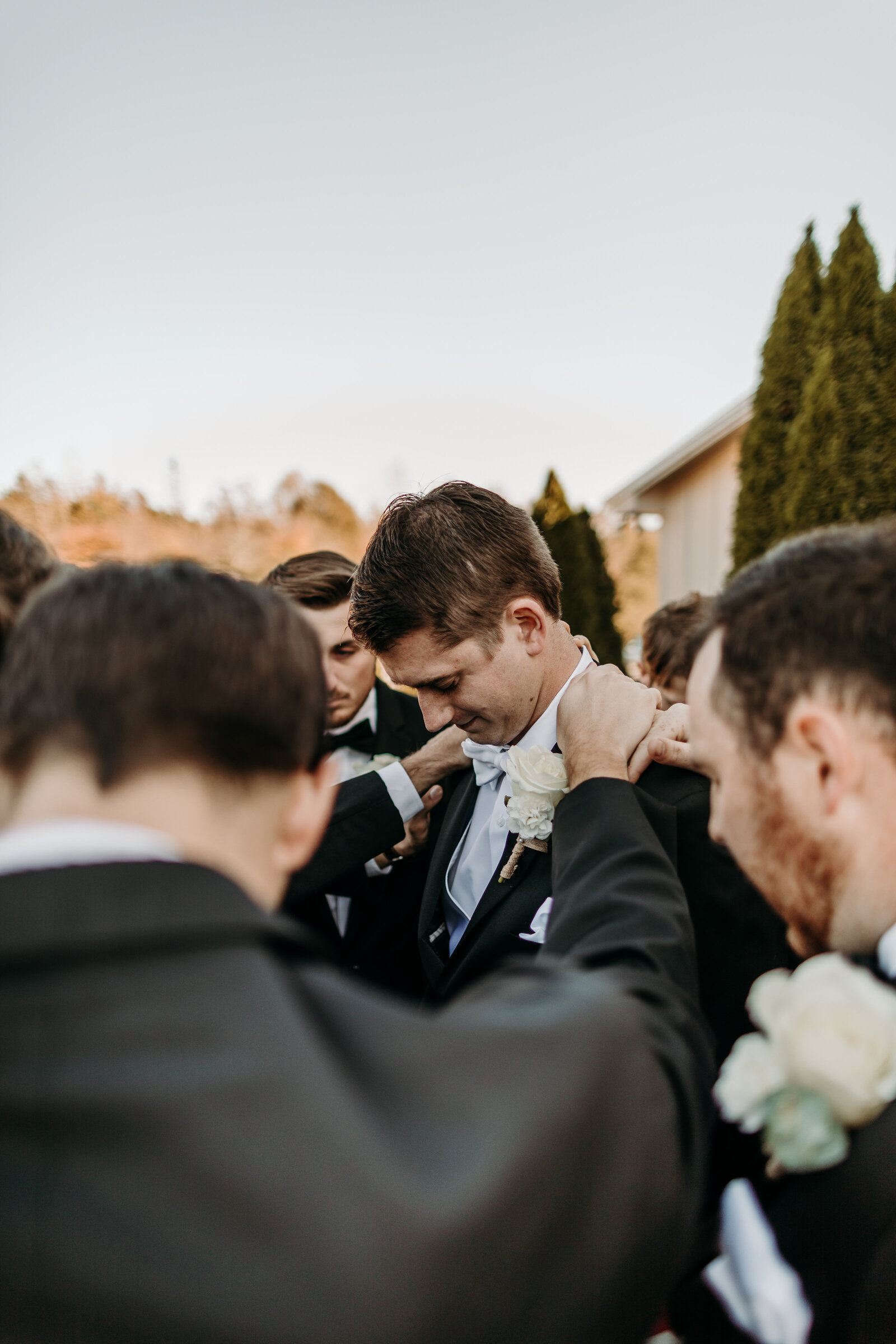J.Michelle Photography photographs groomsmen pray for groom at vintage oaks farm wedding in Athens, Ga