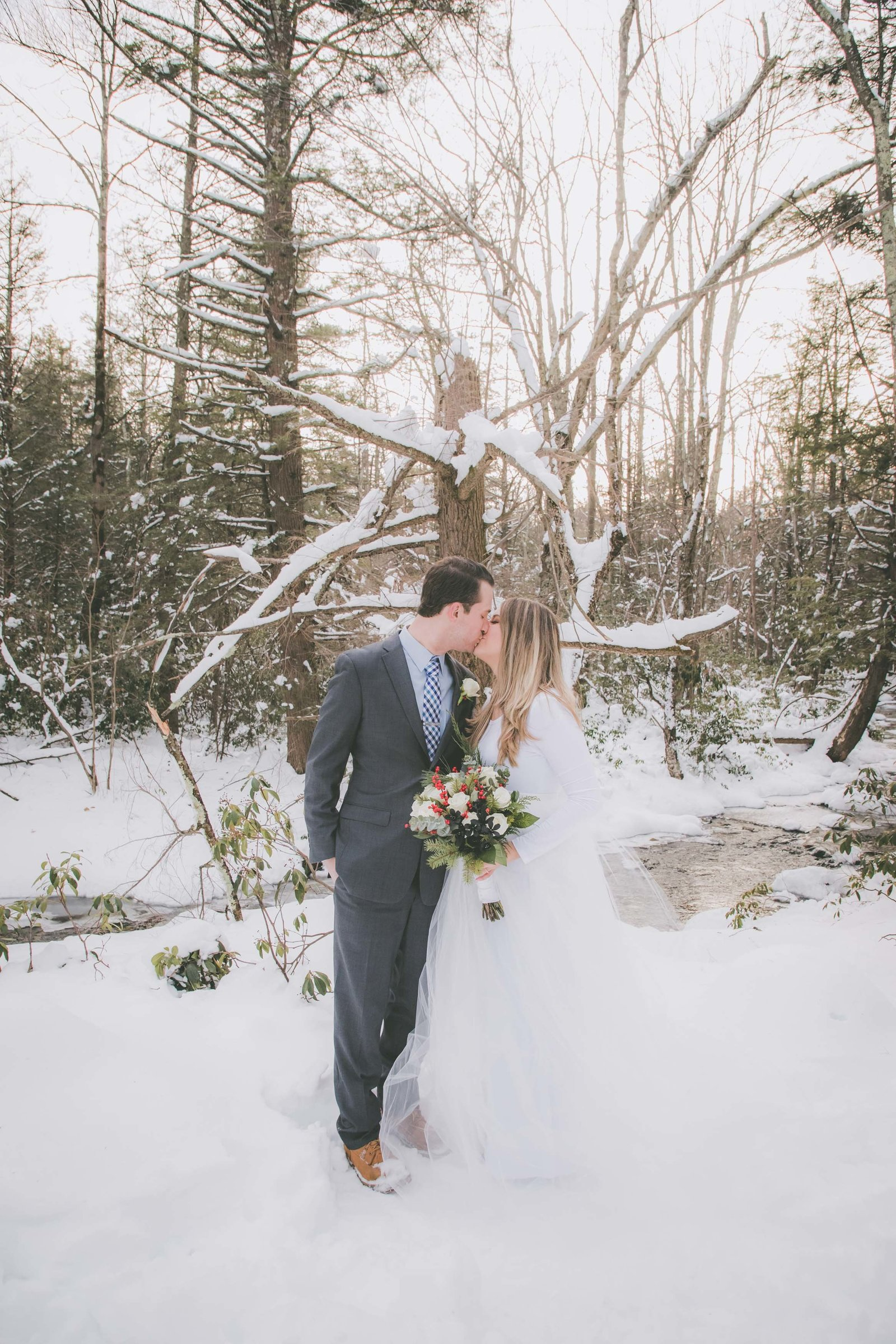 Bride and groom kiss among snow covered trees and ground.