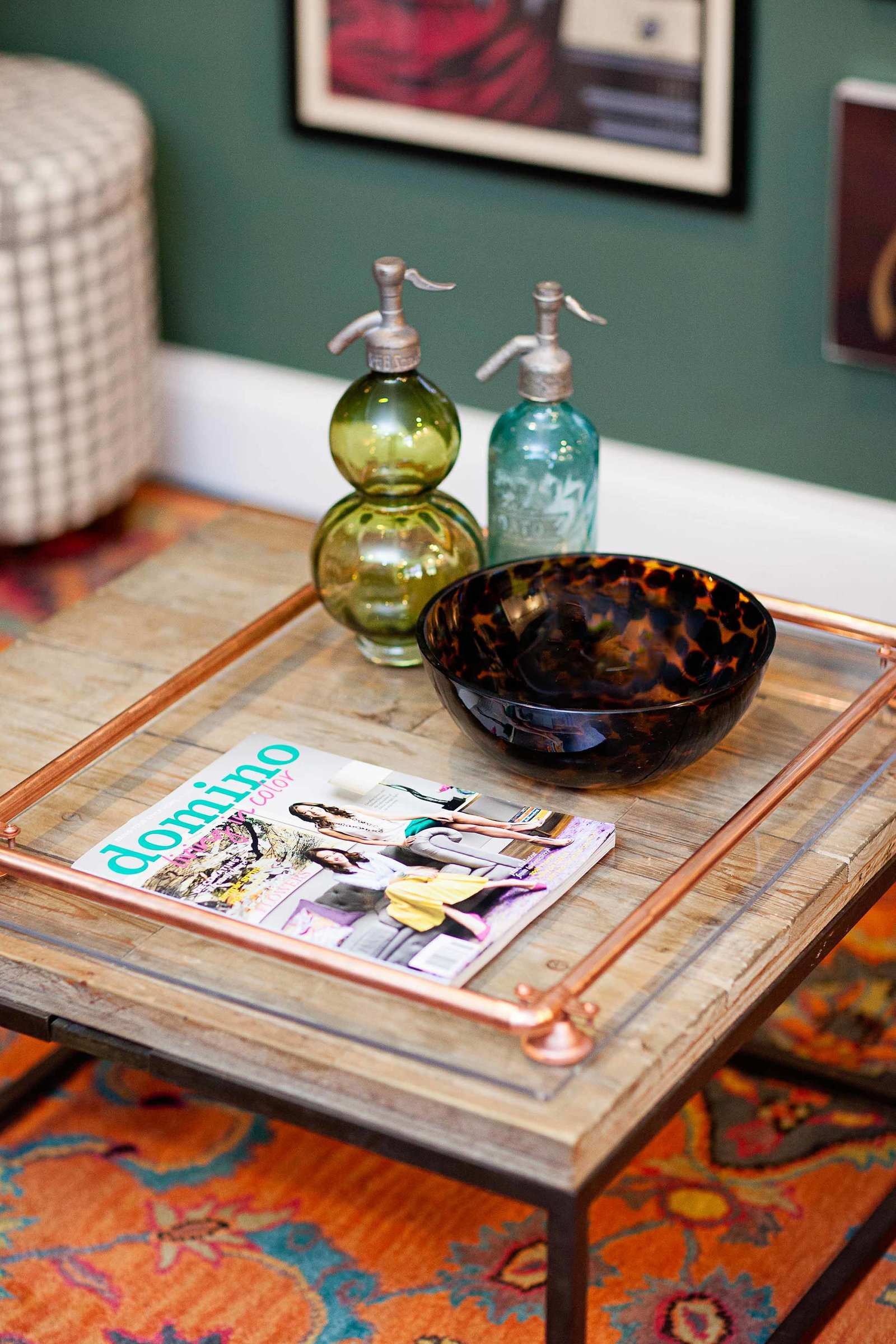 A coffee table with glass dishes and a domino magazine.