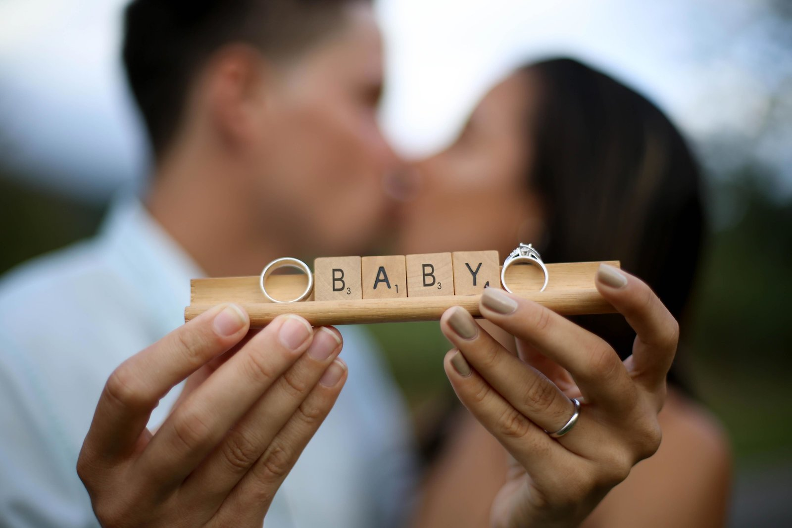 "Couple holding scrabble tiles spelling ""baby"". Photo by Ross Photography, Trinidad, W.I.."