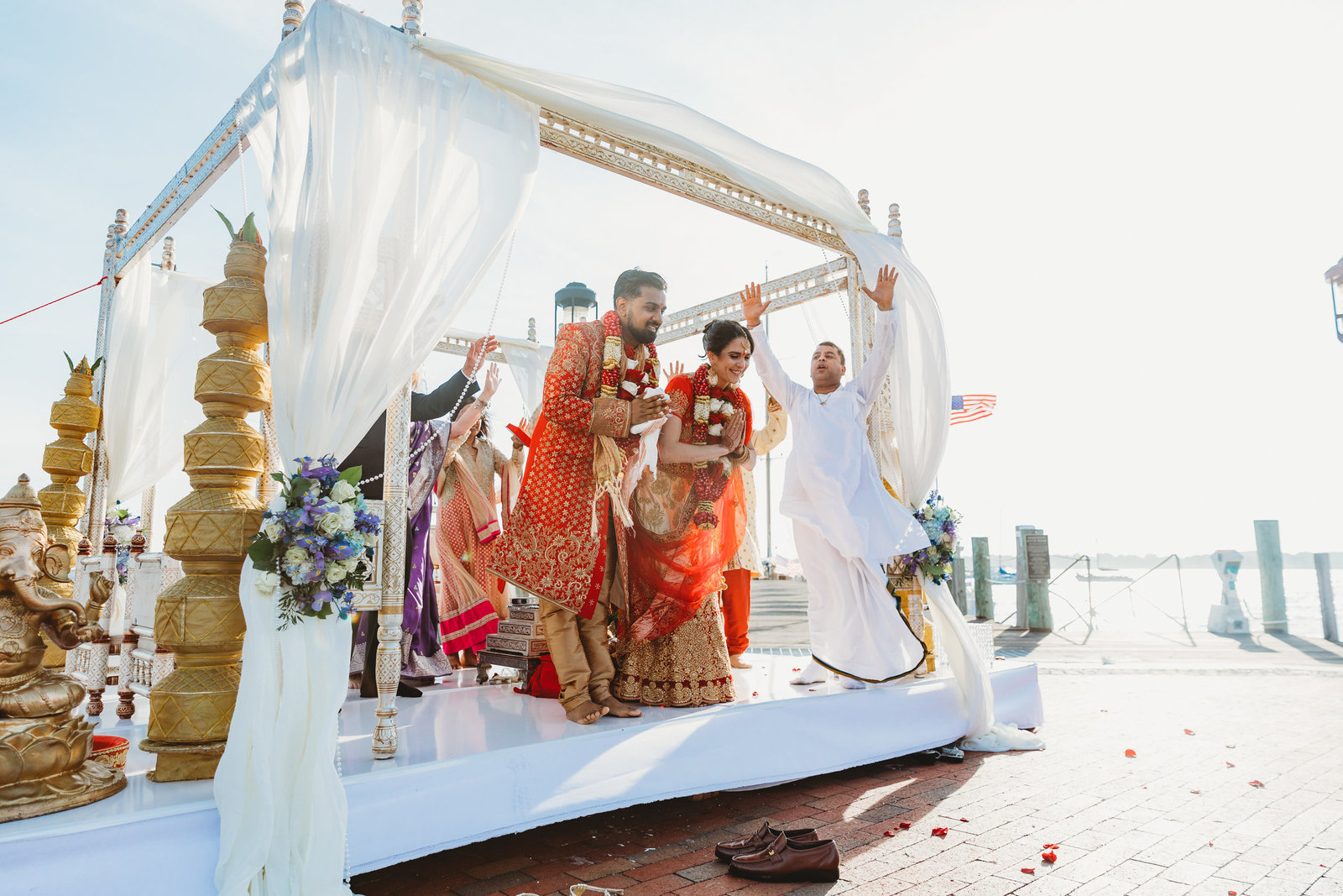 indian wedding couple bow to the crowd during ceremony