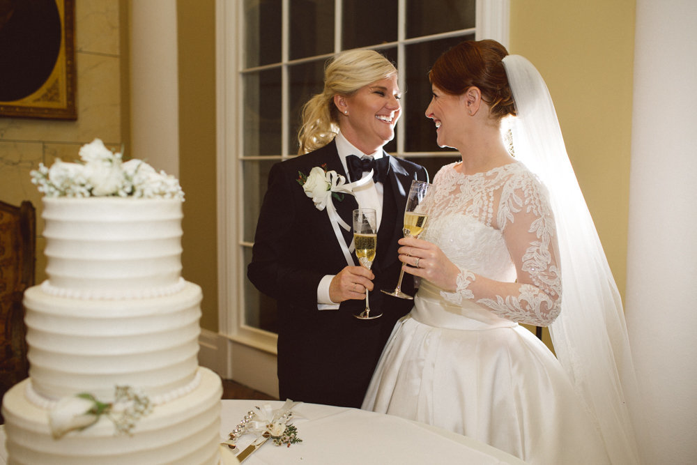 Hemingbough St Francisville Reception for Lesbian couple smile as they toast champagne on their wedding day beside their wedding cake