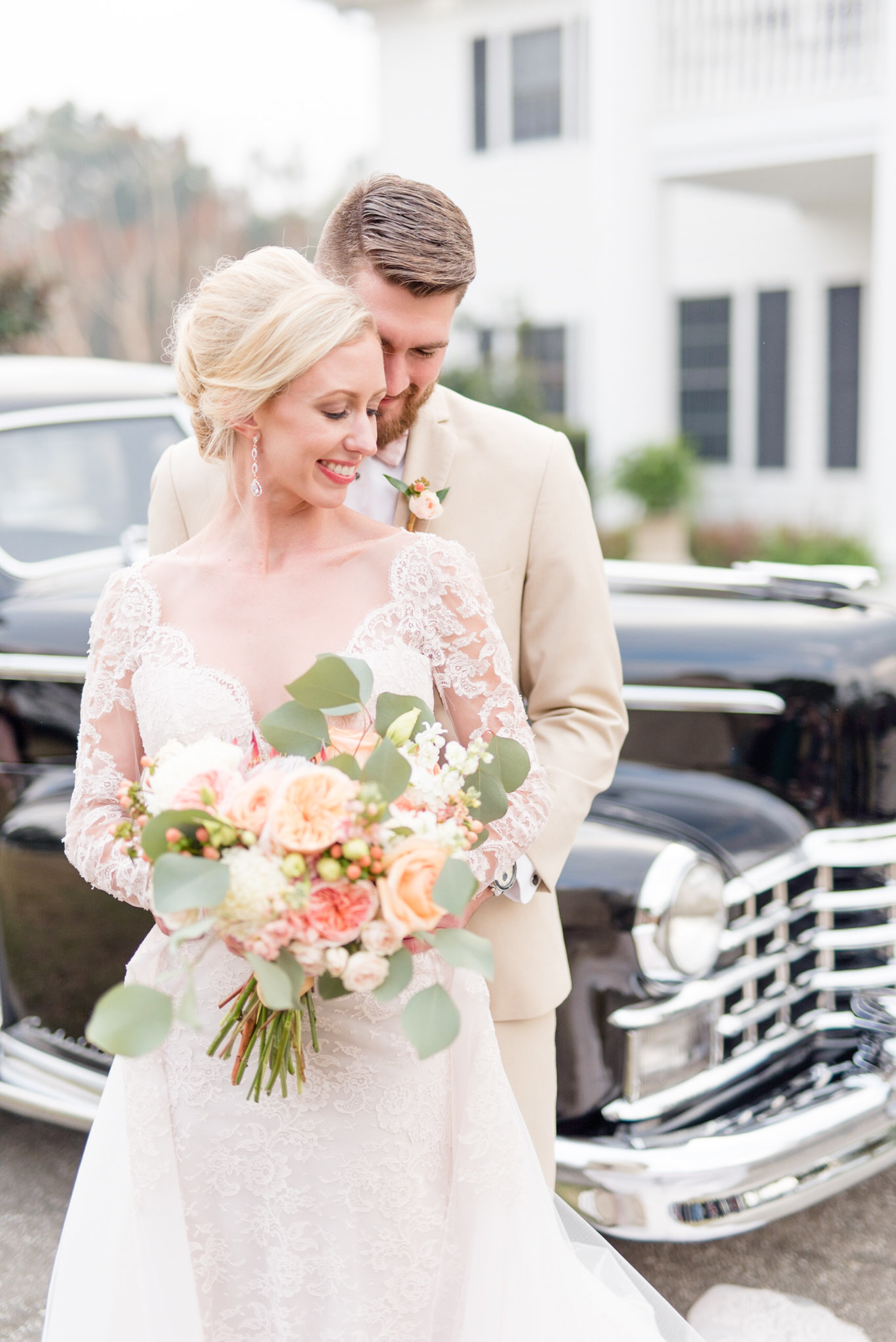 Bride and groom stand in front of classic car.