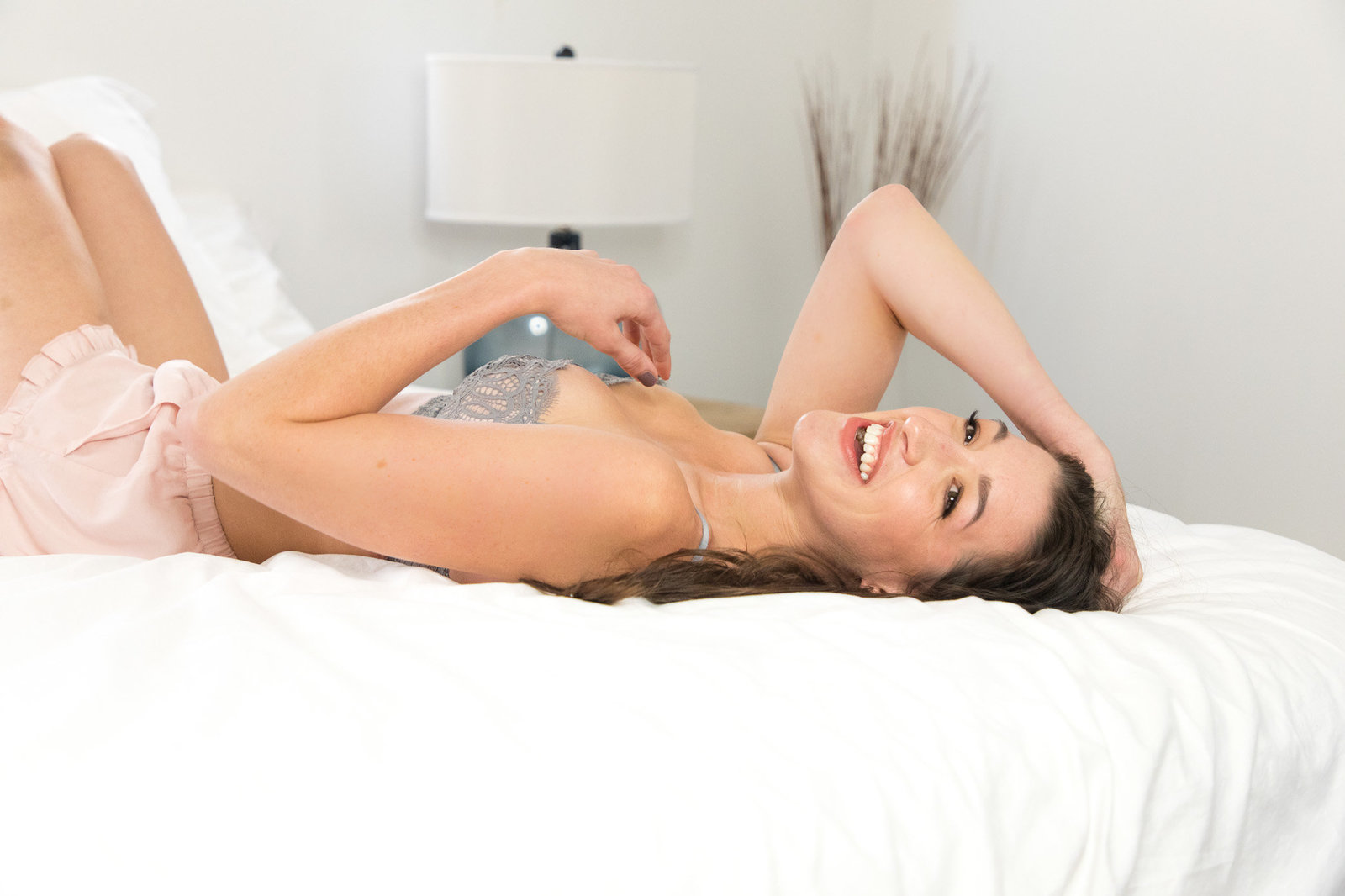 Woman lying on white bed in cute pajamas smiling