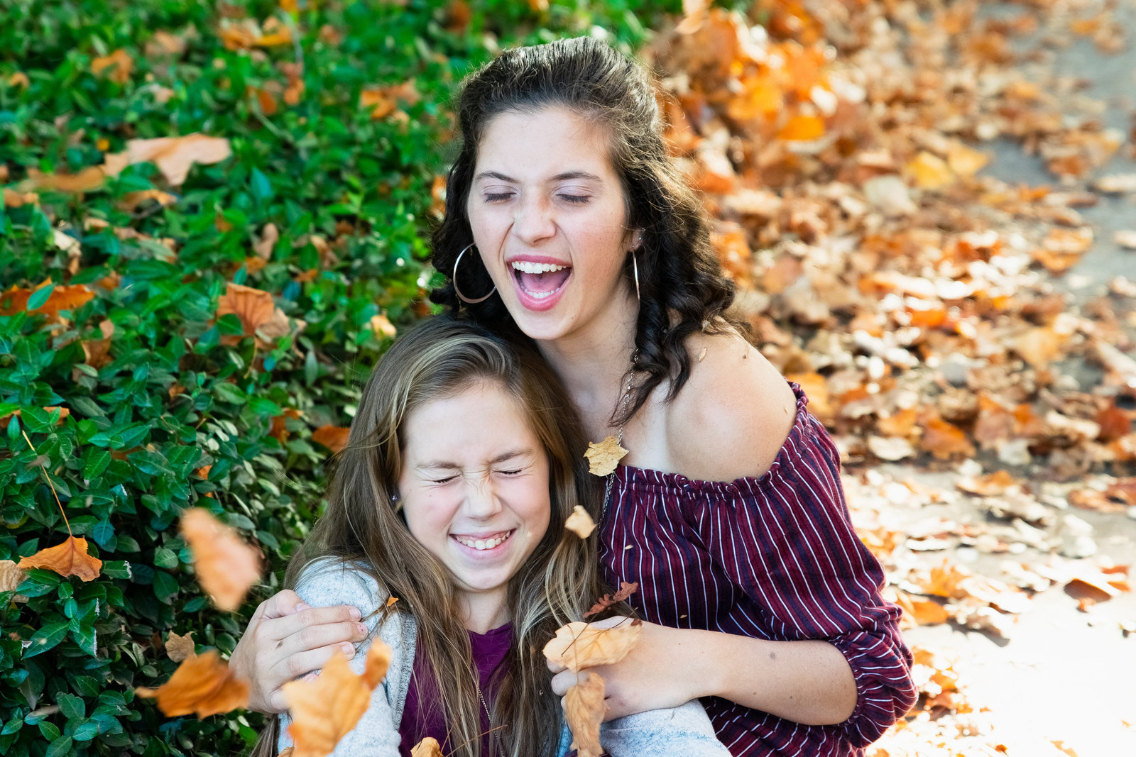 two sisters laughing with leaves falling on them