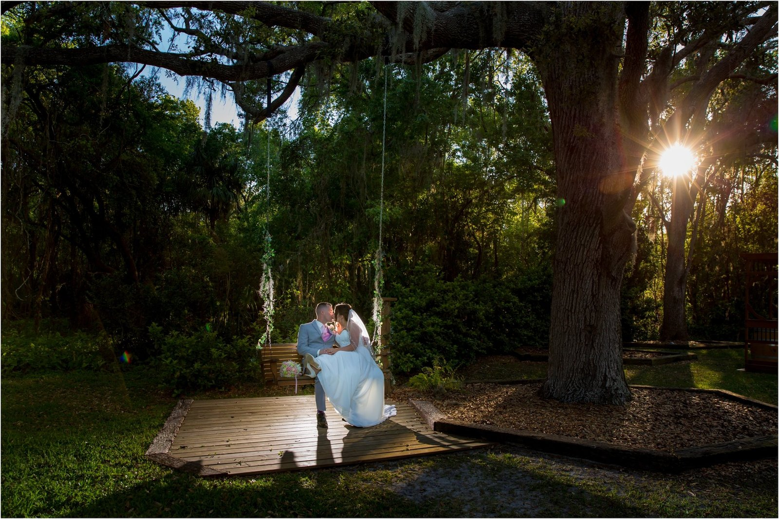 Bakers Ranch Wedding Photography of bride and groom on the swing under the live oak trees with sun peeking between the trees