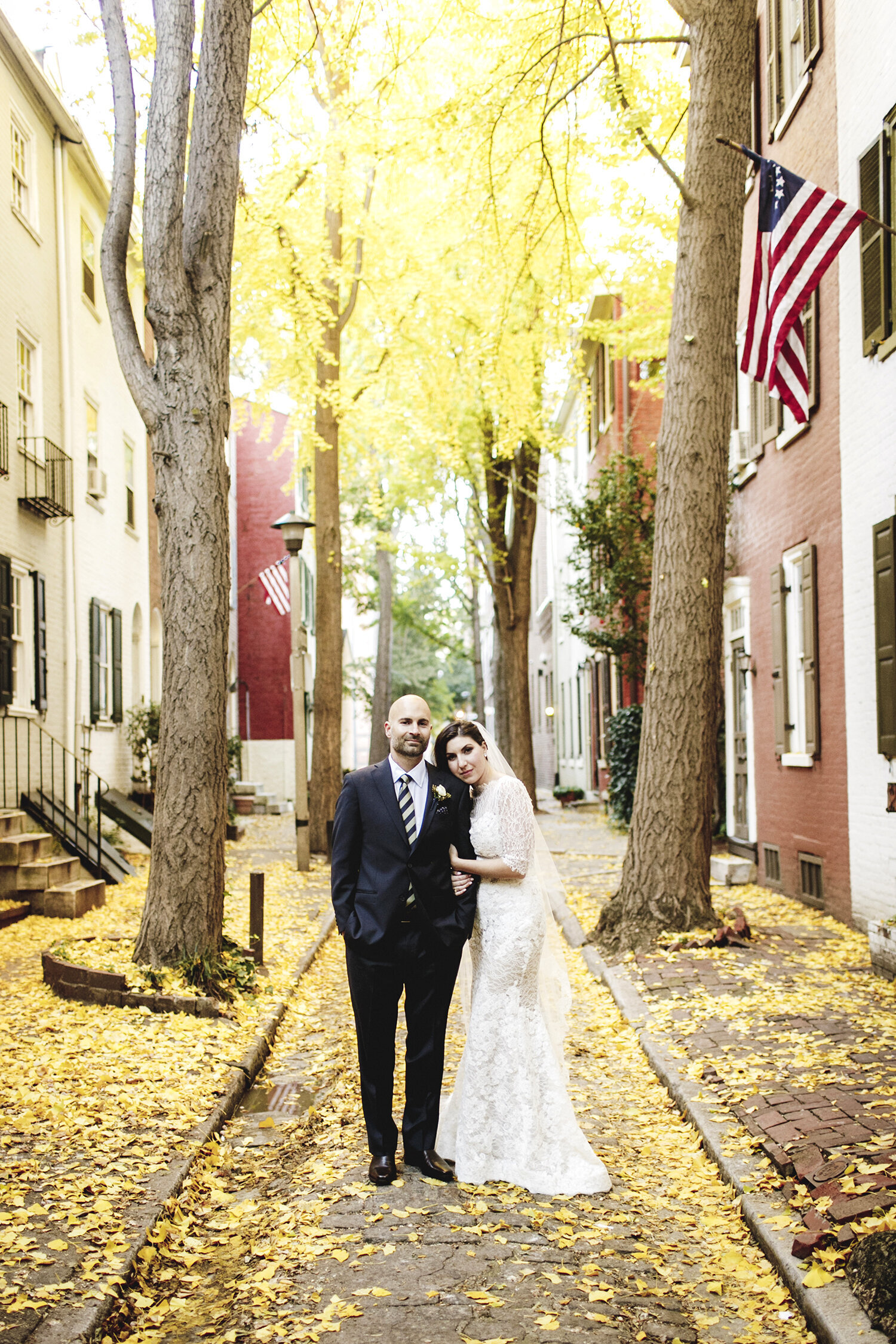 bride and groom with yellow fall leaves on city street