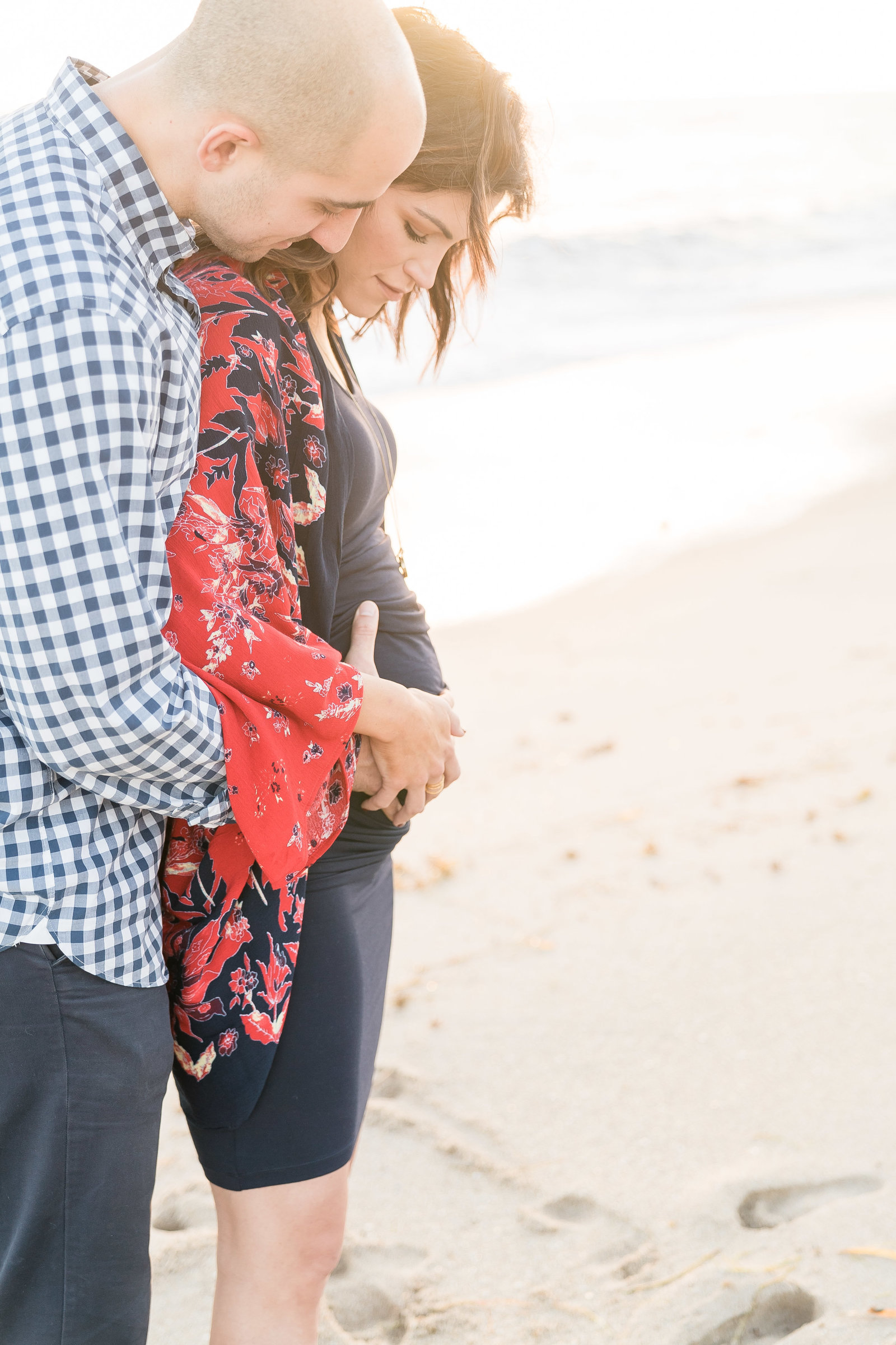 Charlotte Maternity photographer shot of couple on beach holding belly