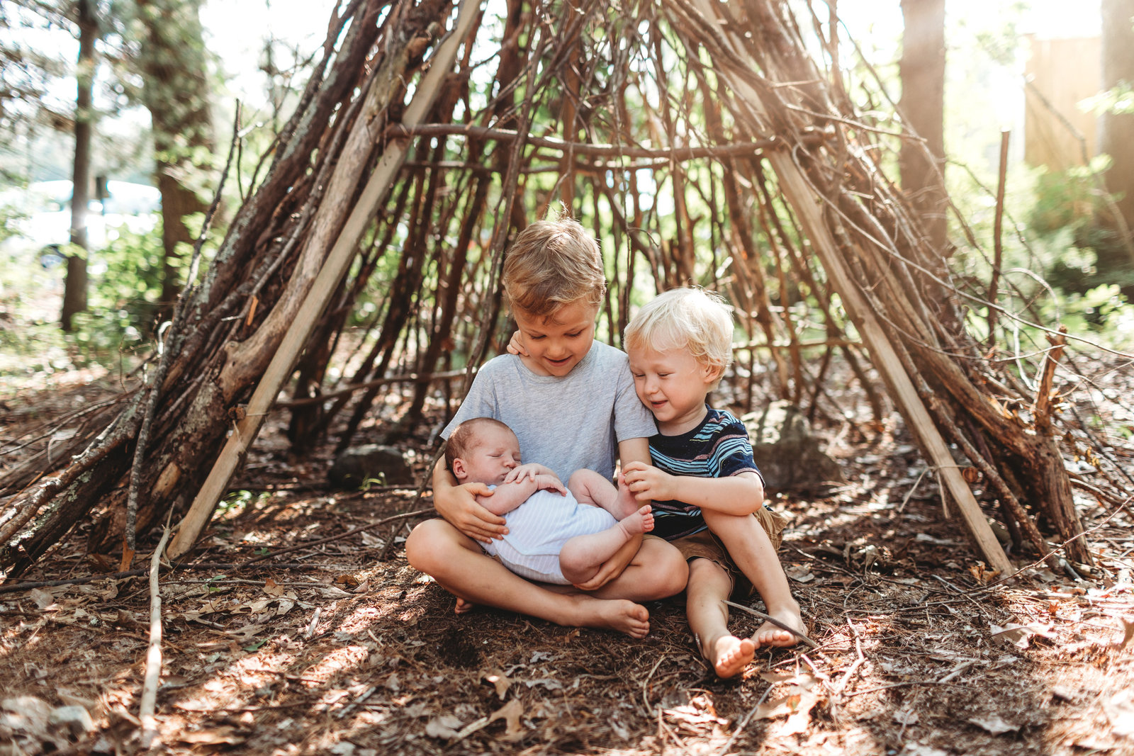 brothers hold new baby outdoors by stick teepee in lincoln ma