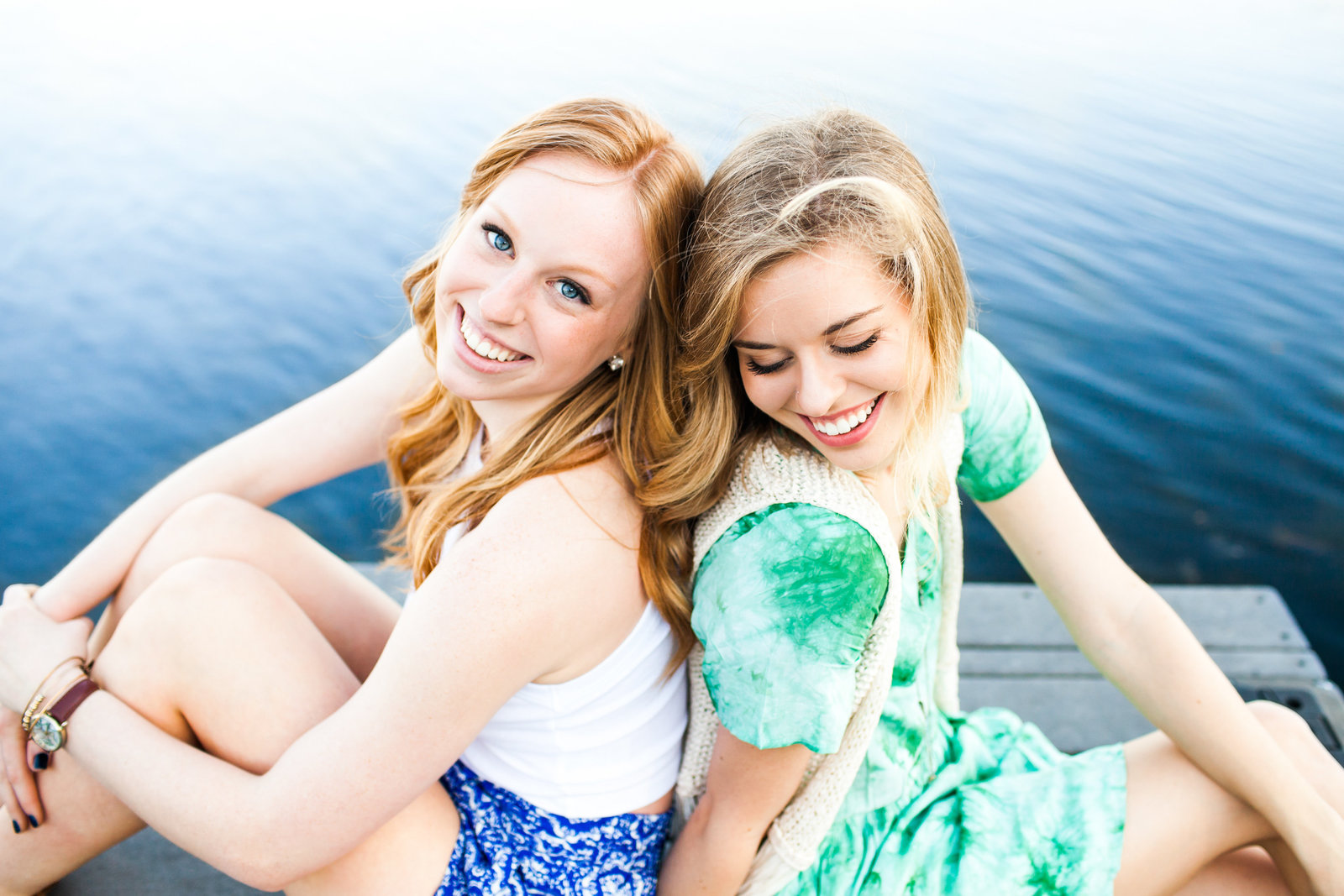 Sisters back to back laughing on a dock by blue water