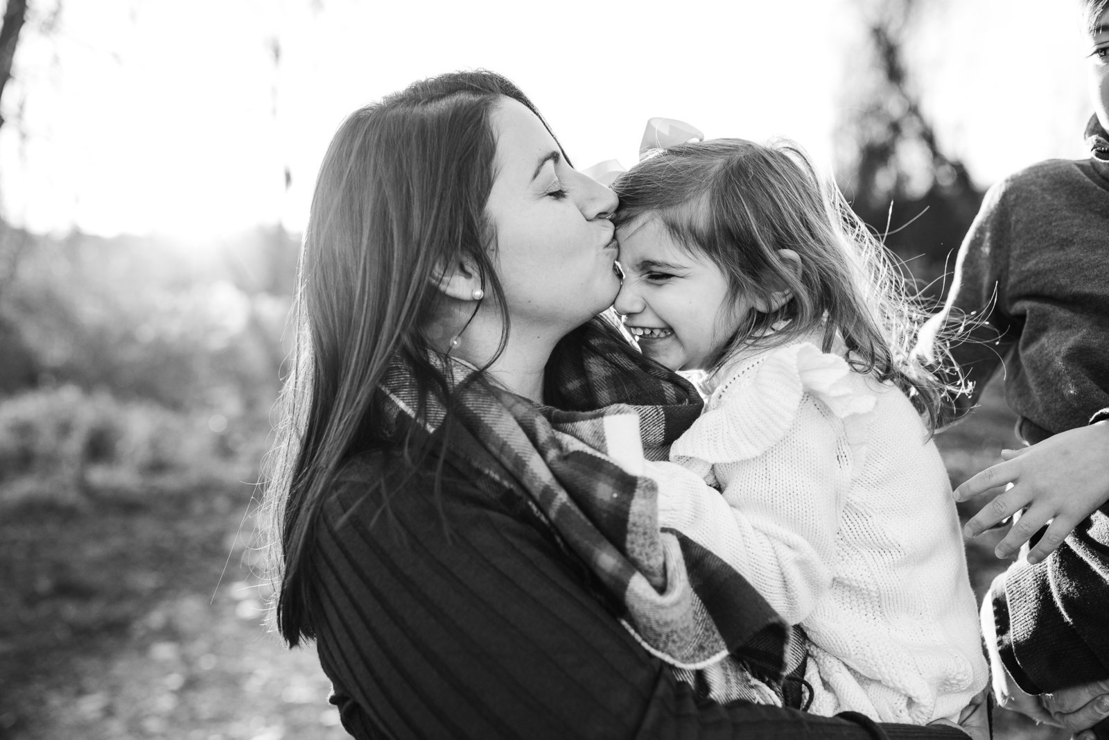 mom kisses forehead of laughing girl during family photos in framingham ma