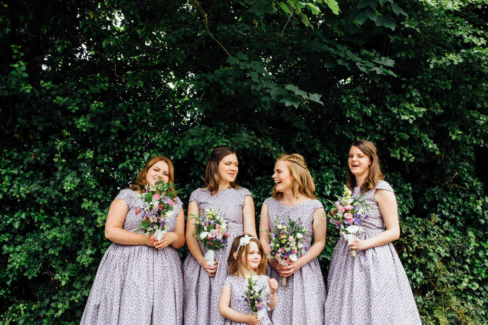 Smiling bridesmaids in purple handmade dresses against leafy Suffolk backdrop waiting for bride to arrive