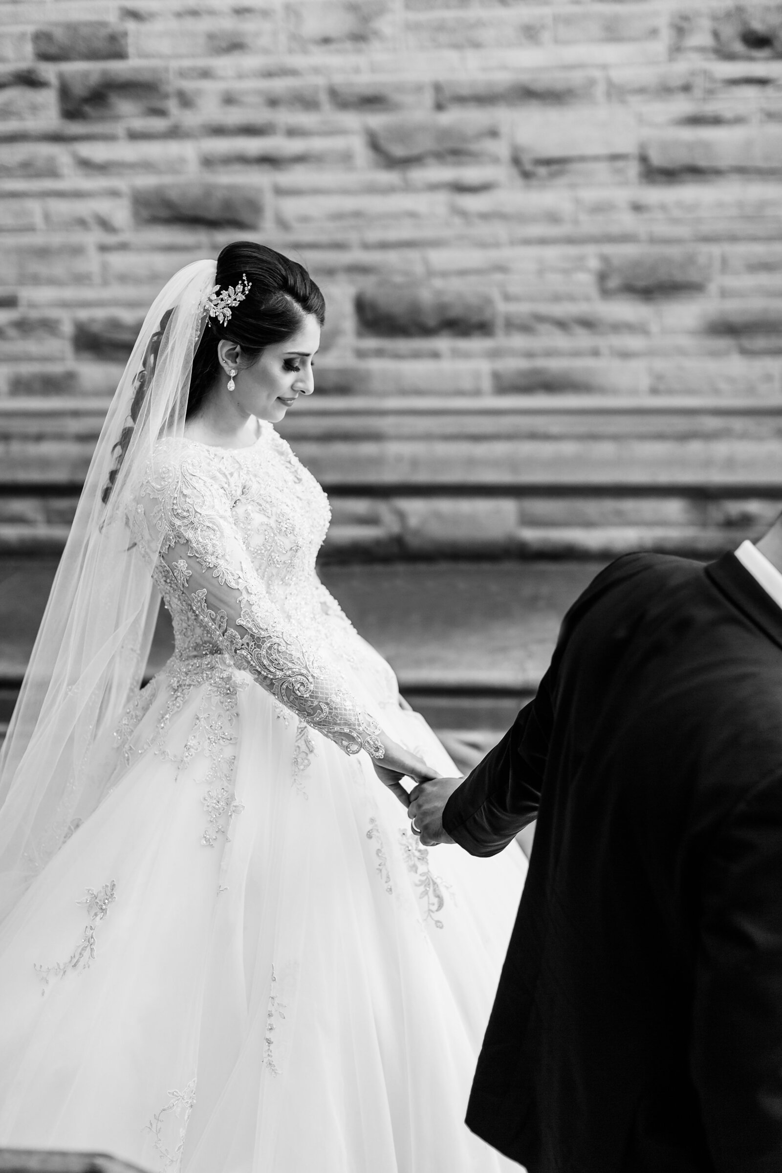 Lebanese-bride-follows-her-husband-down-the-steps-at-western-university-during-their-wedding-portraits