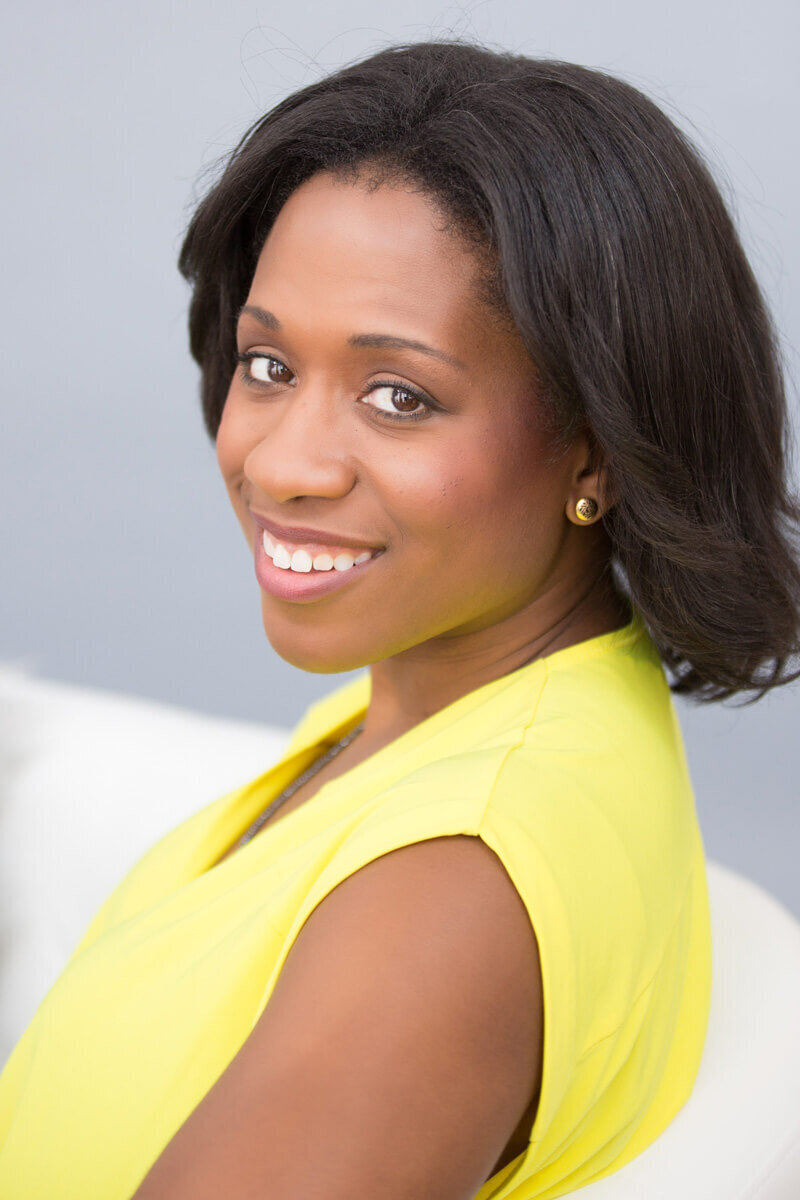 Professional headshot of woman in a yellow shirt looking over shoulder at the camera