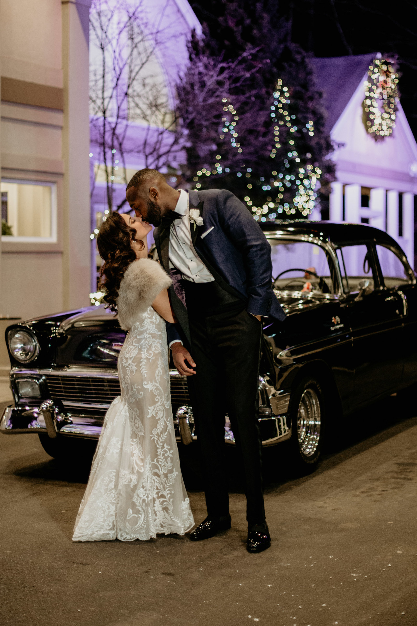 bride and groom kiss in front of a vintage car.